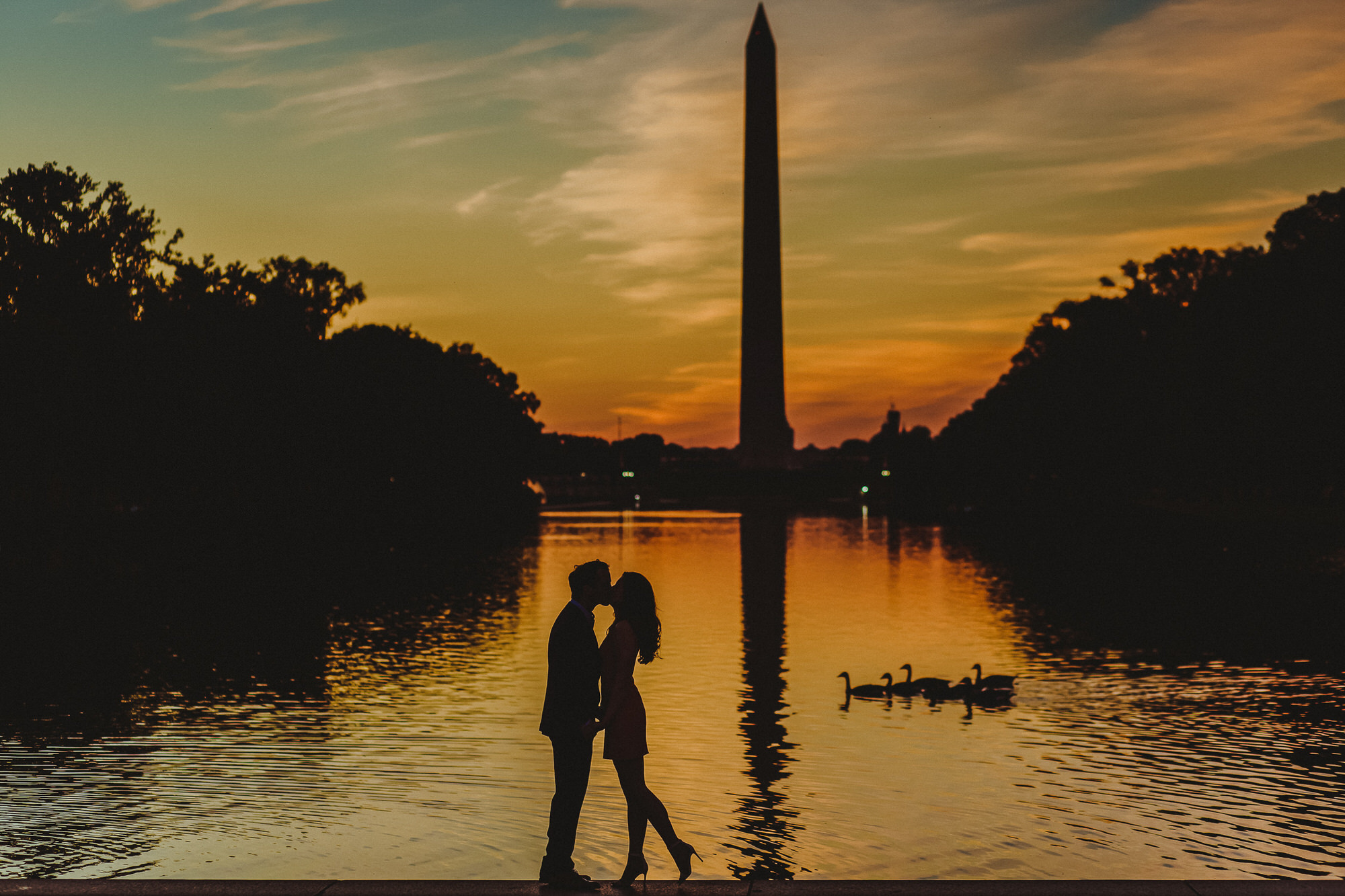 Silhouette of couple against national monument at sunset - photo by Ken Pak