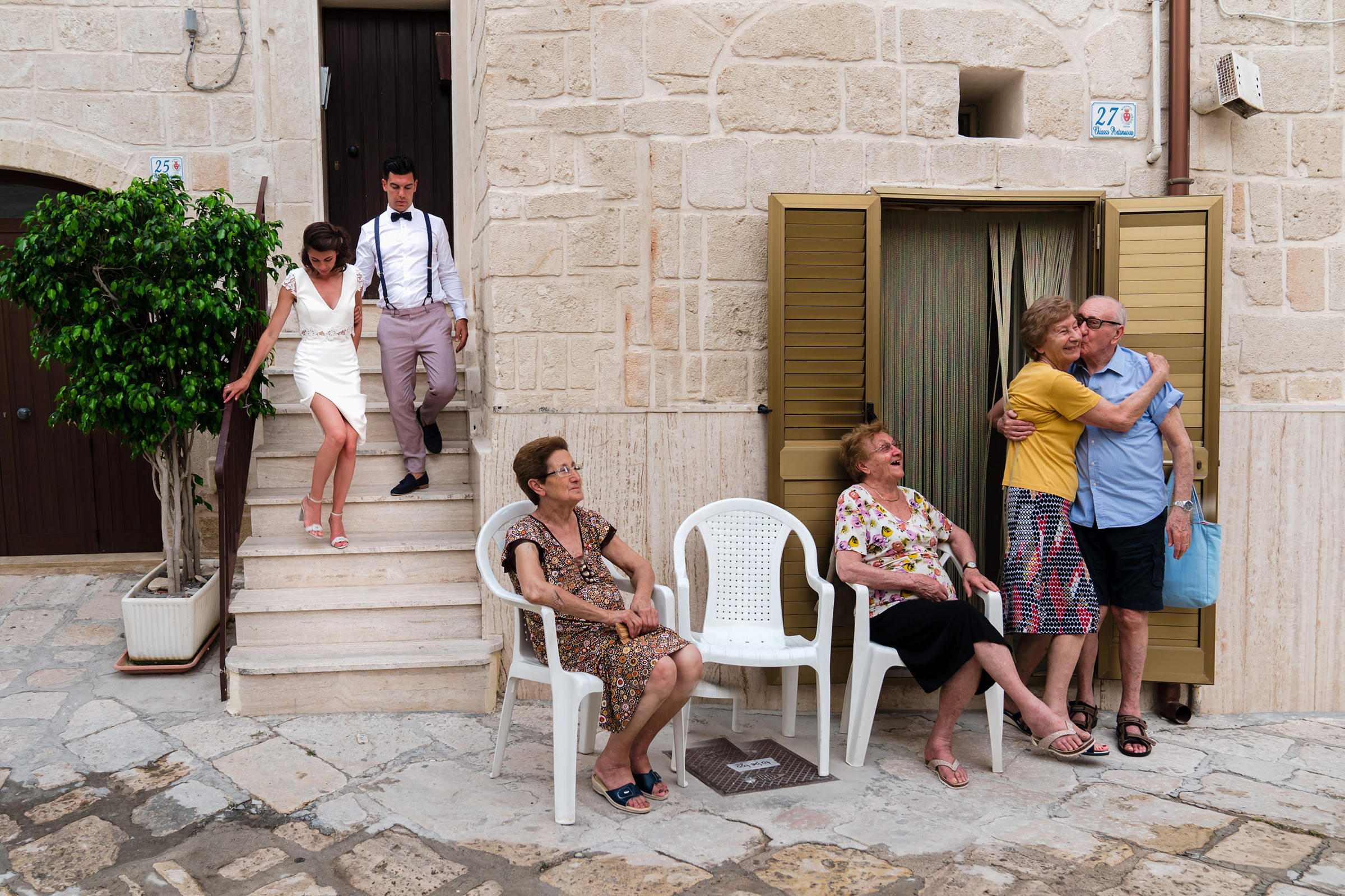 Bride and groom walk down stairs as strangers kiss on street, photo by Philippe Swiggers