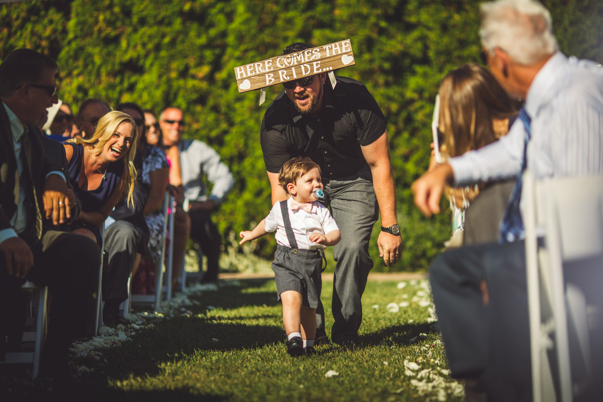 Funny photo of dad and ringbearer walking down the aisle, by Jeff Newsom