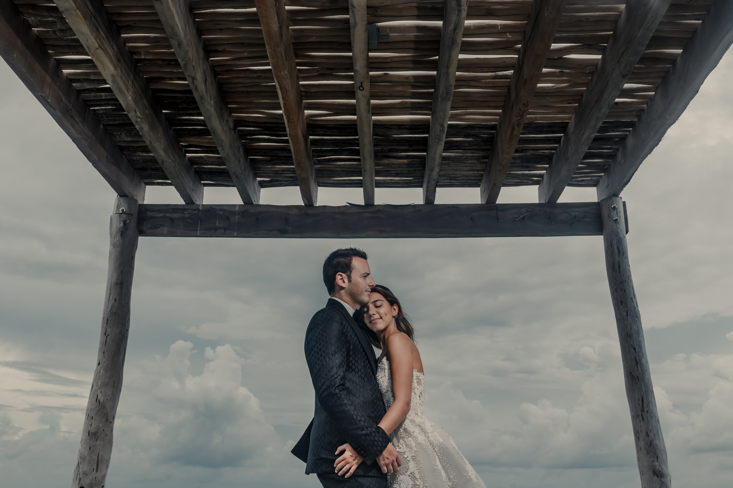 Sweet couple portrait under wooden arbor - photo by El Marco Rojo