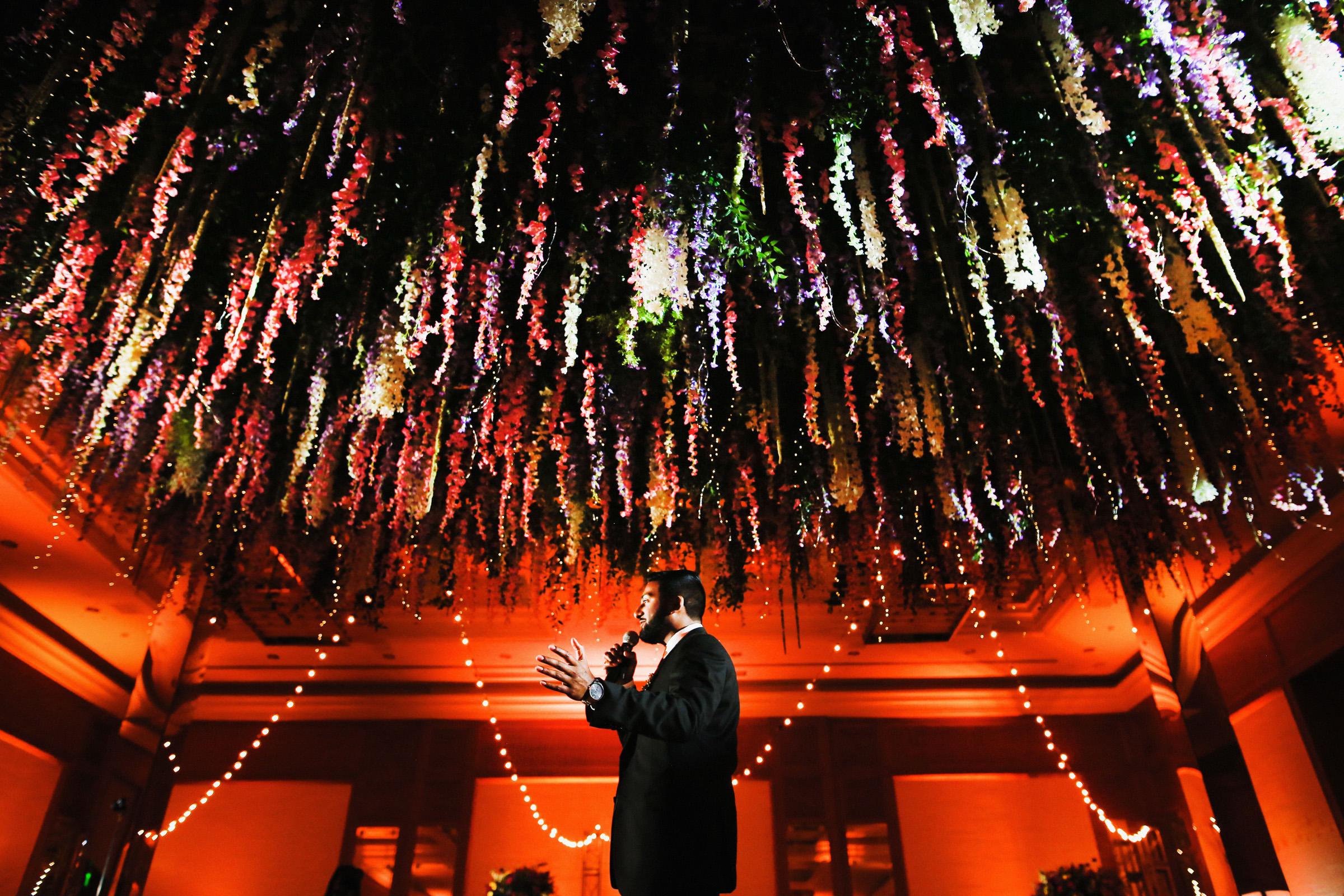 Best man toast under elaborate ceiling floral decor by Franck Boutonnet