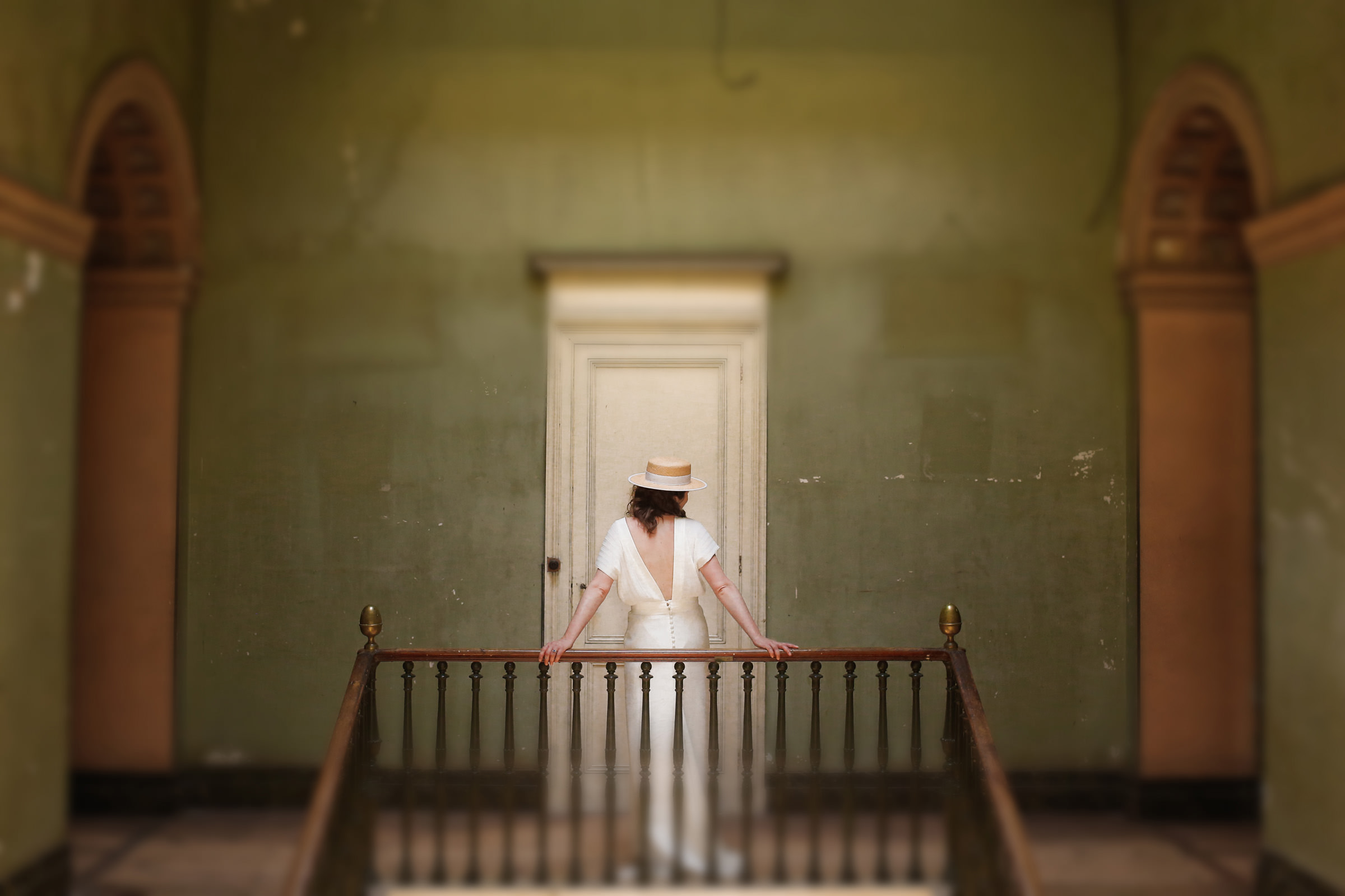 Bride in hat and backless modern bridal gown in old building, by Franck Boutonnet
