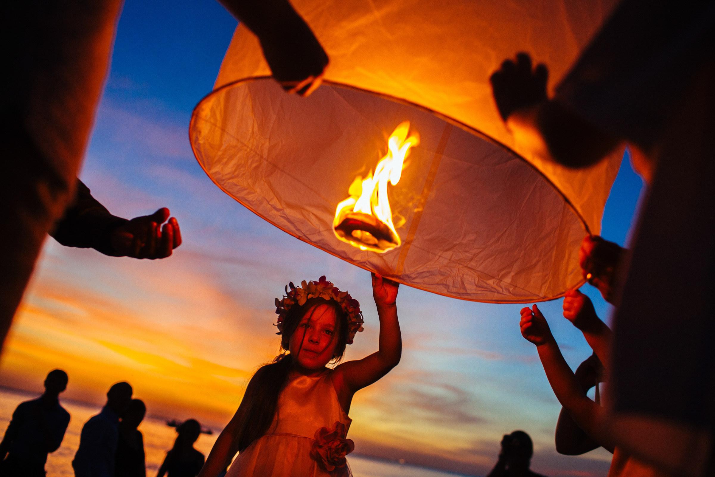 Flower girl against lantern - Photo by Wainwright Weddings