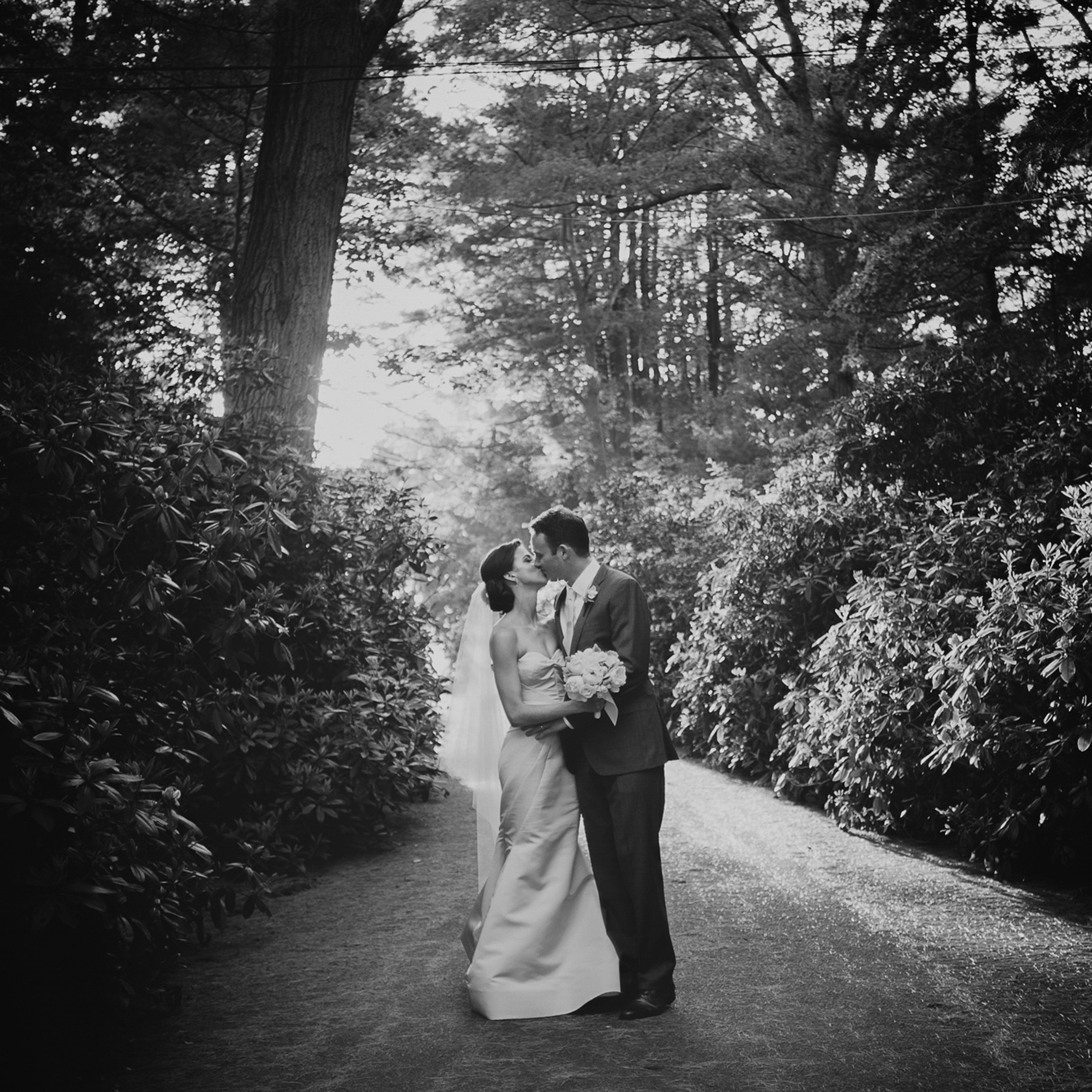 Black and white film portrait of couple on forest path - photo by Richard Israel Photography