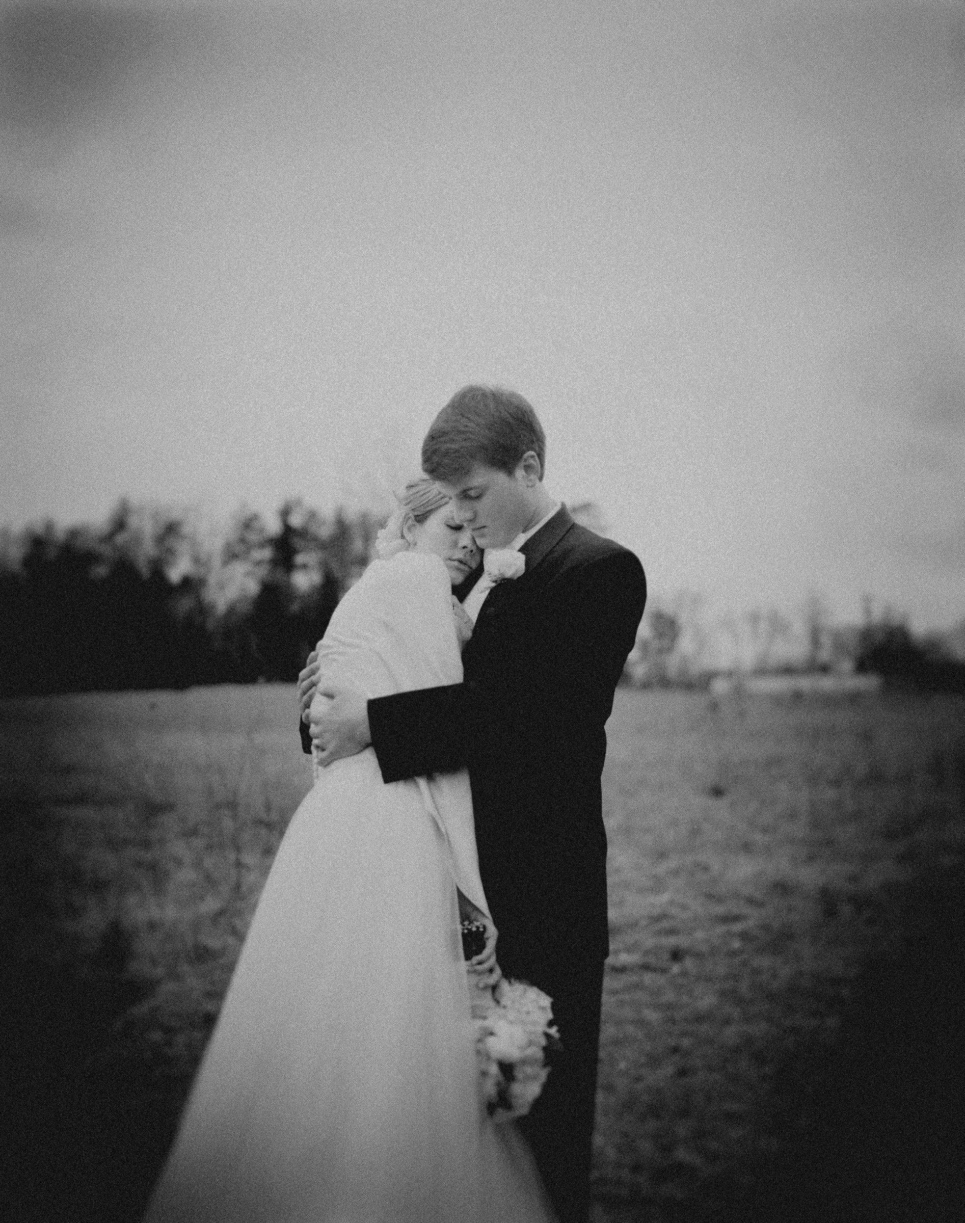 Sepia portrait of bride and groom hugging by Richard Israel Photography
