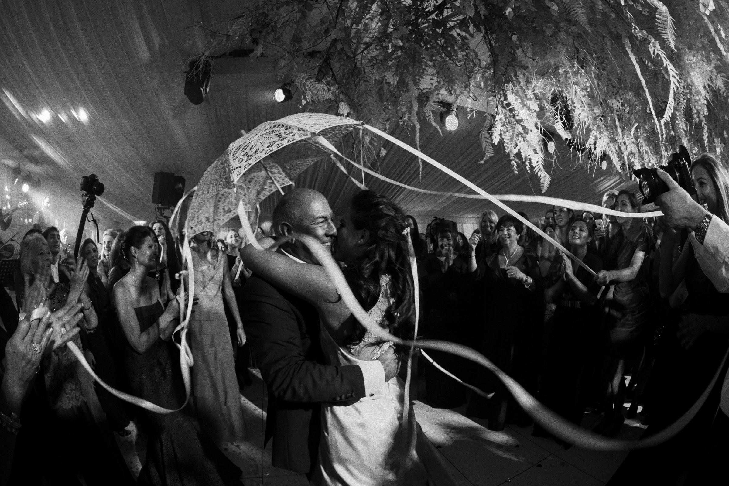Bride and groom under parasol by Jeff Ascough