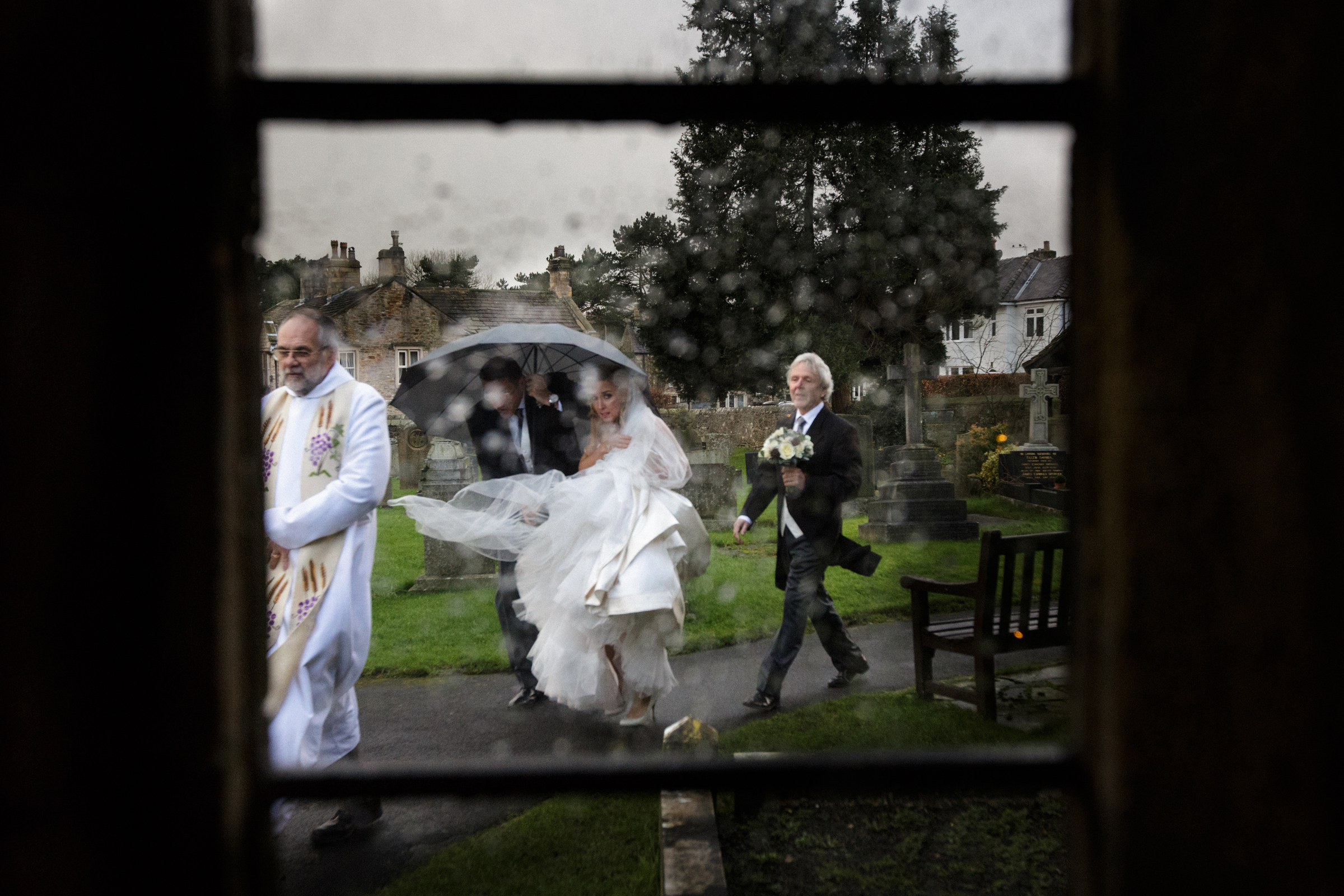 Bride and groom walking through church grounds - photo by Jeff Ascough