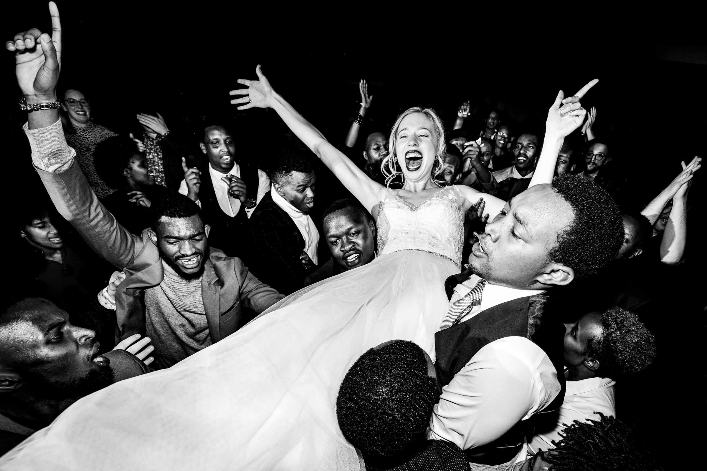 Bride crowdsurfing on top of guests Photo by JOS & TREE