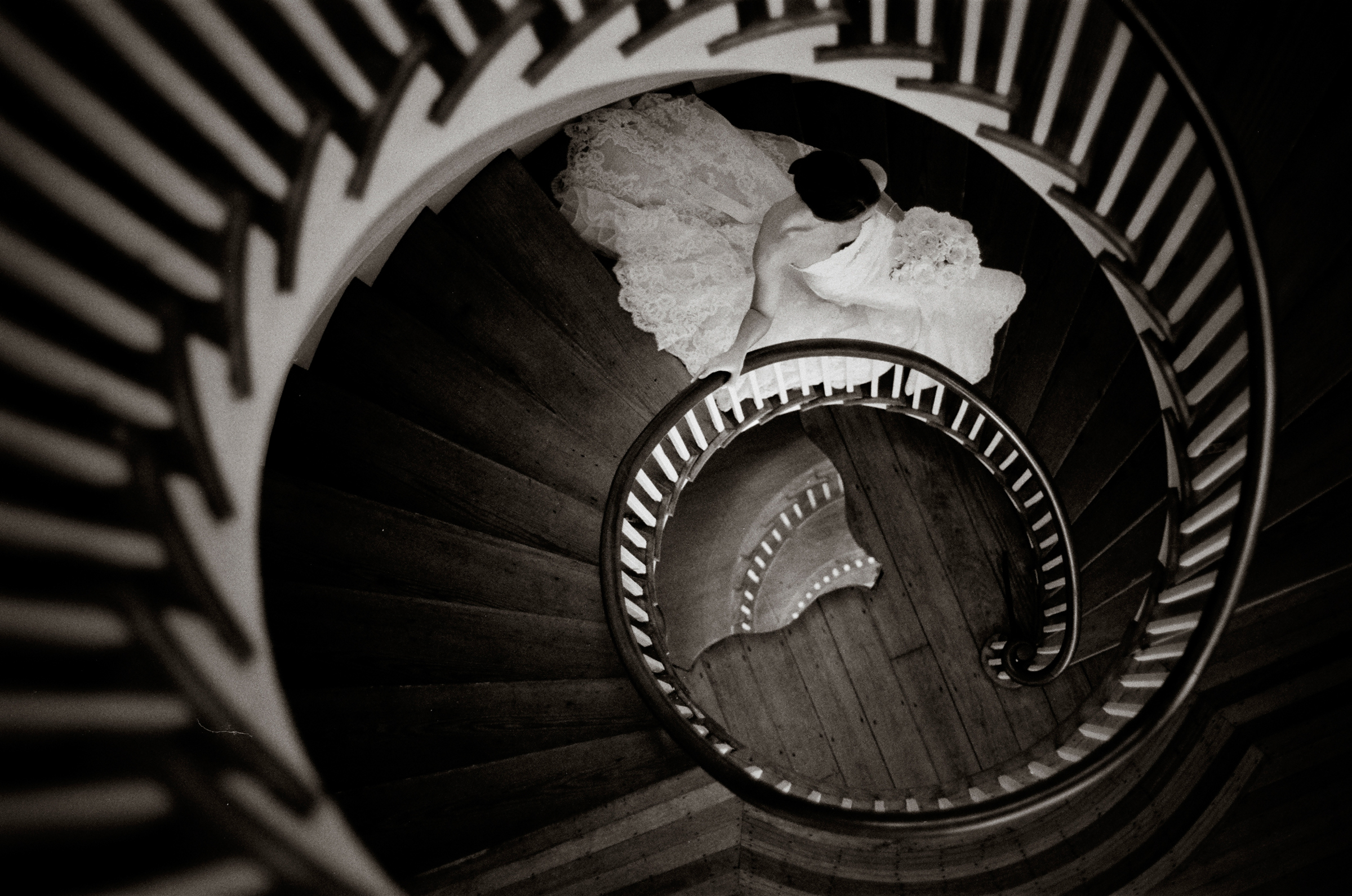 Bride descends wooden spiral stairway - photo by Richard Israel Photography