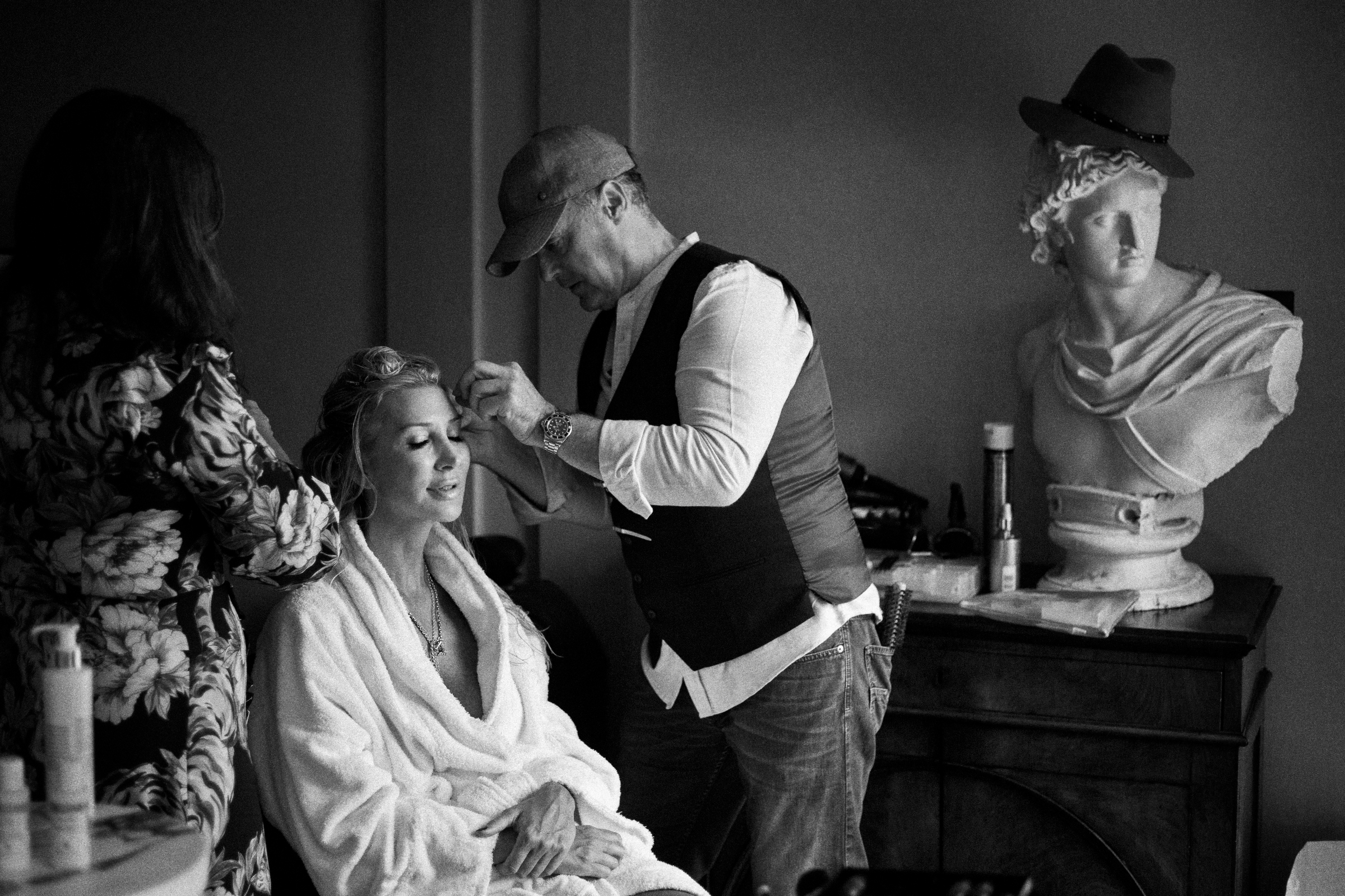 Bride gets her make up done near greek bust with top hat - photo by Jeff Ascough