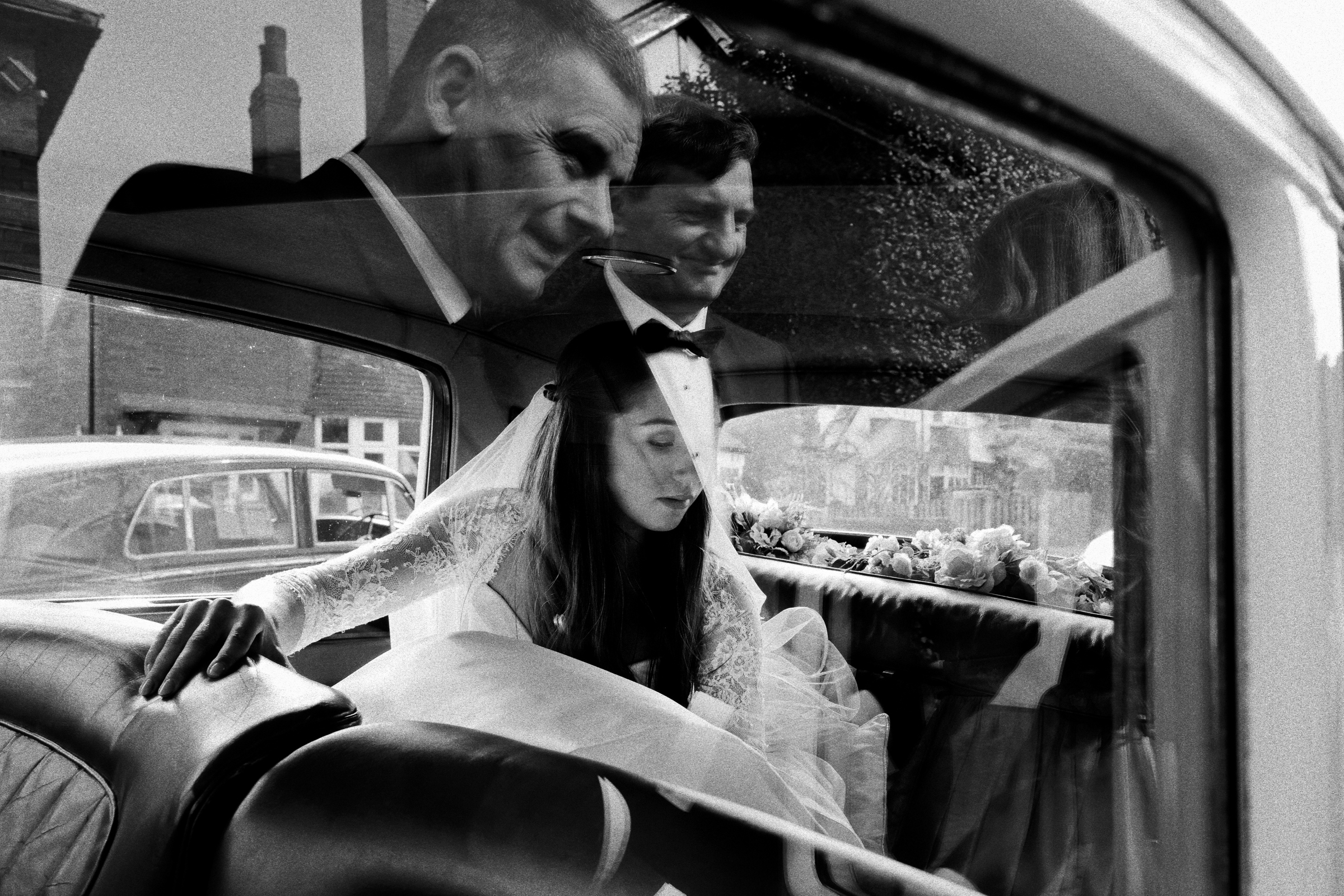 Reflection of father and groom awaiting bride getting out of limo - photo by Jeff Ascough