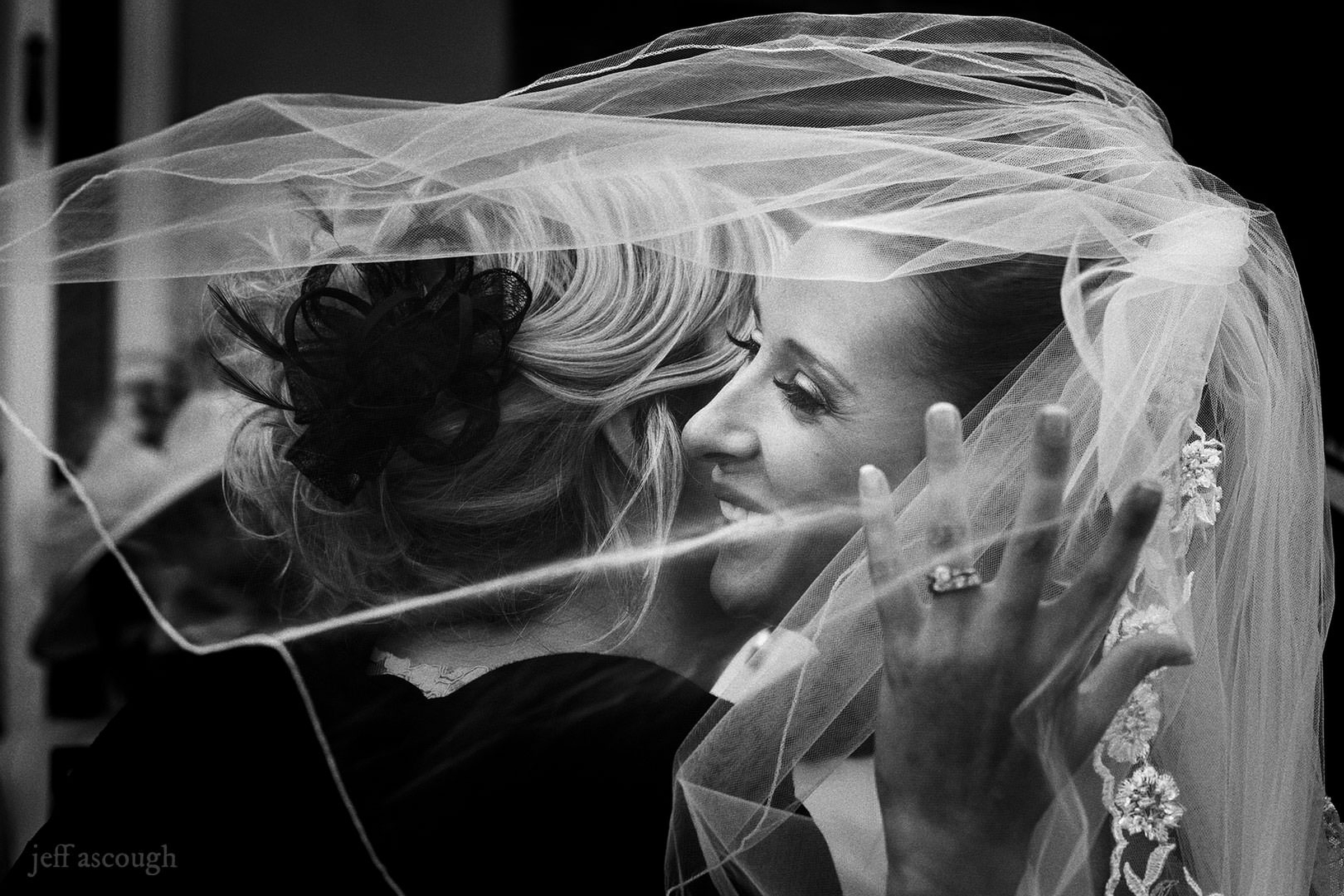 Bride hugs mom under veil by Jeff Ascough