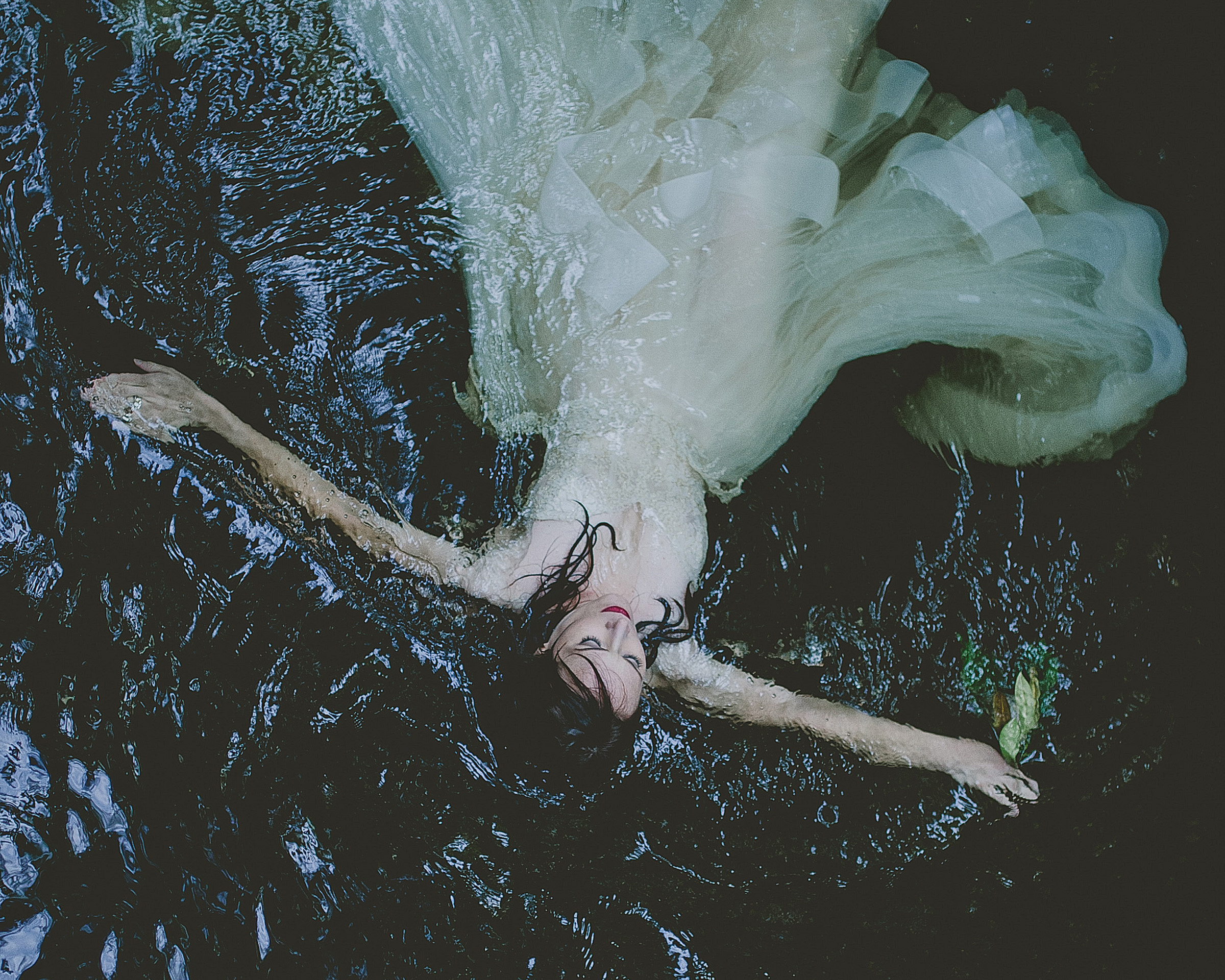 Bride in gown floating in water by Richard Israel