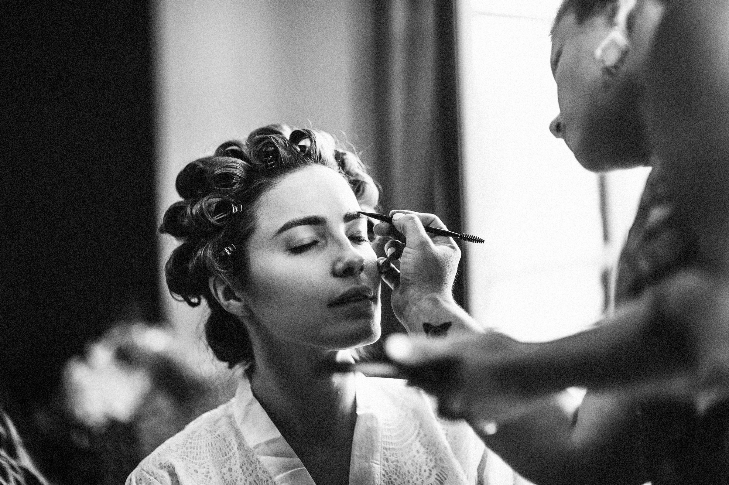 Bride in rollers getting makeup done. Photo by Richard Israel Photography