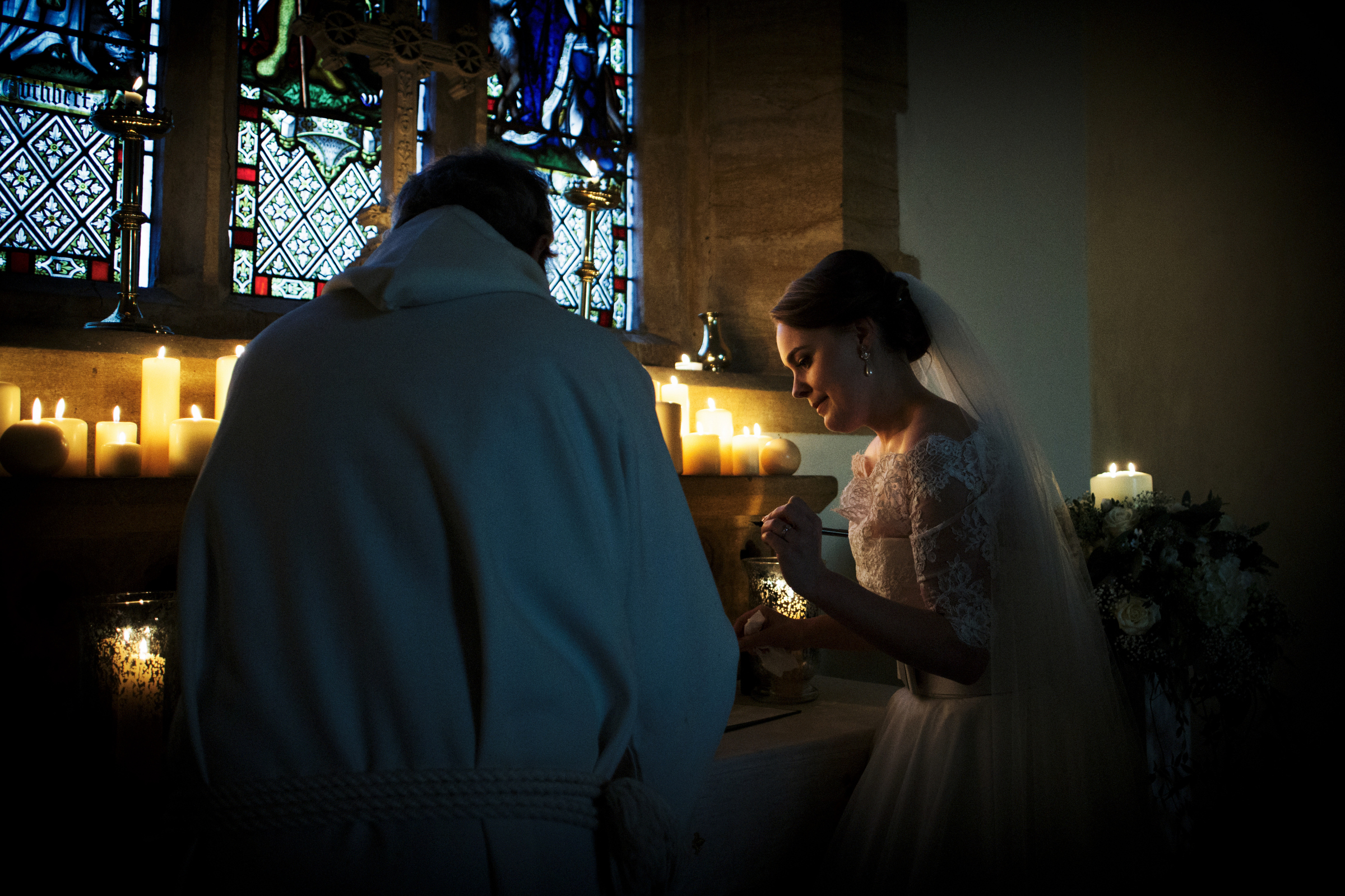 bride lights candle with priest - photo by Jeff Ascough