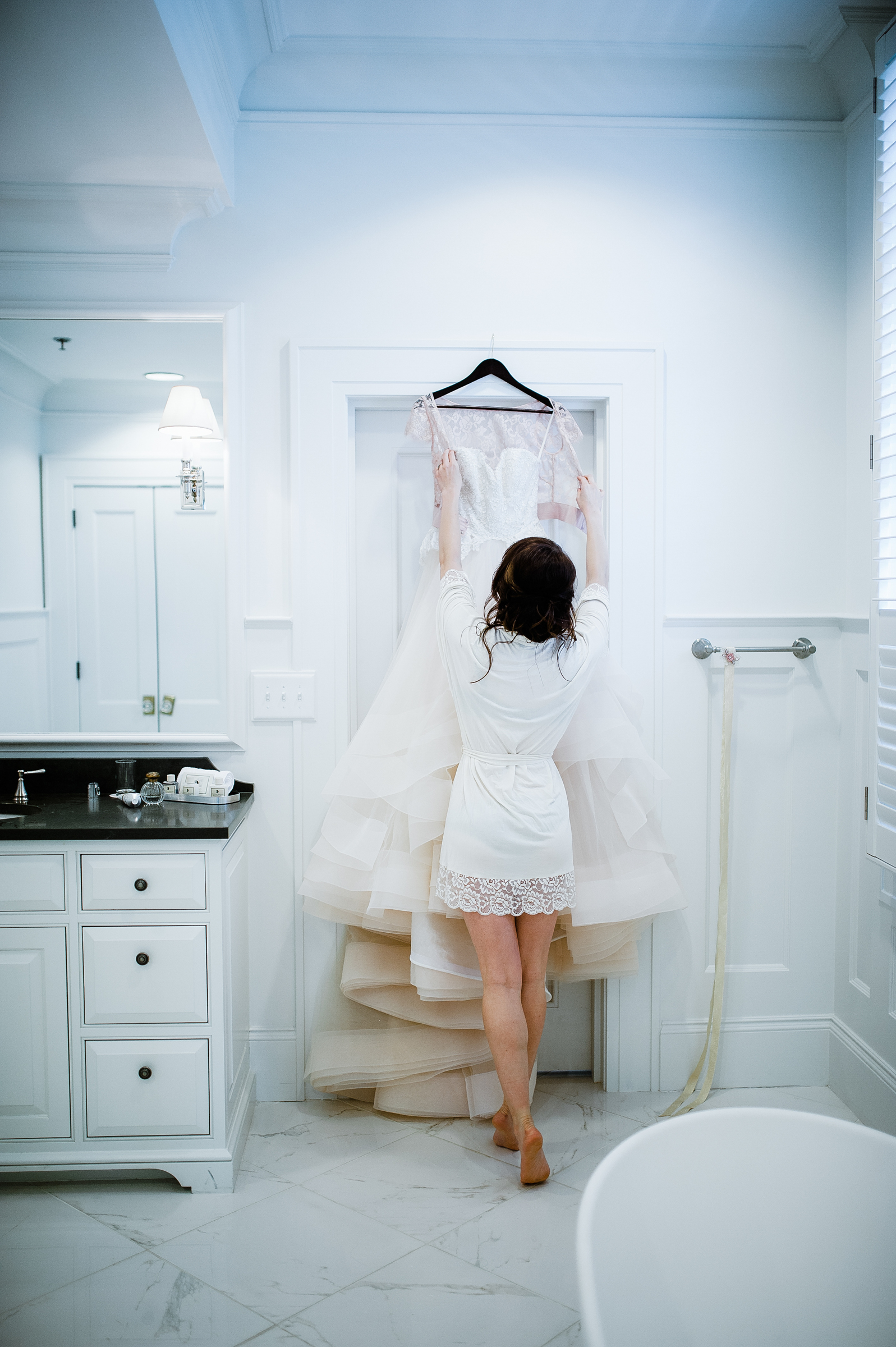 Bride reaches for her wedding gown in bright dressing room - photo by Richard Israel Photography