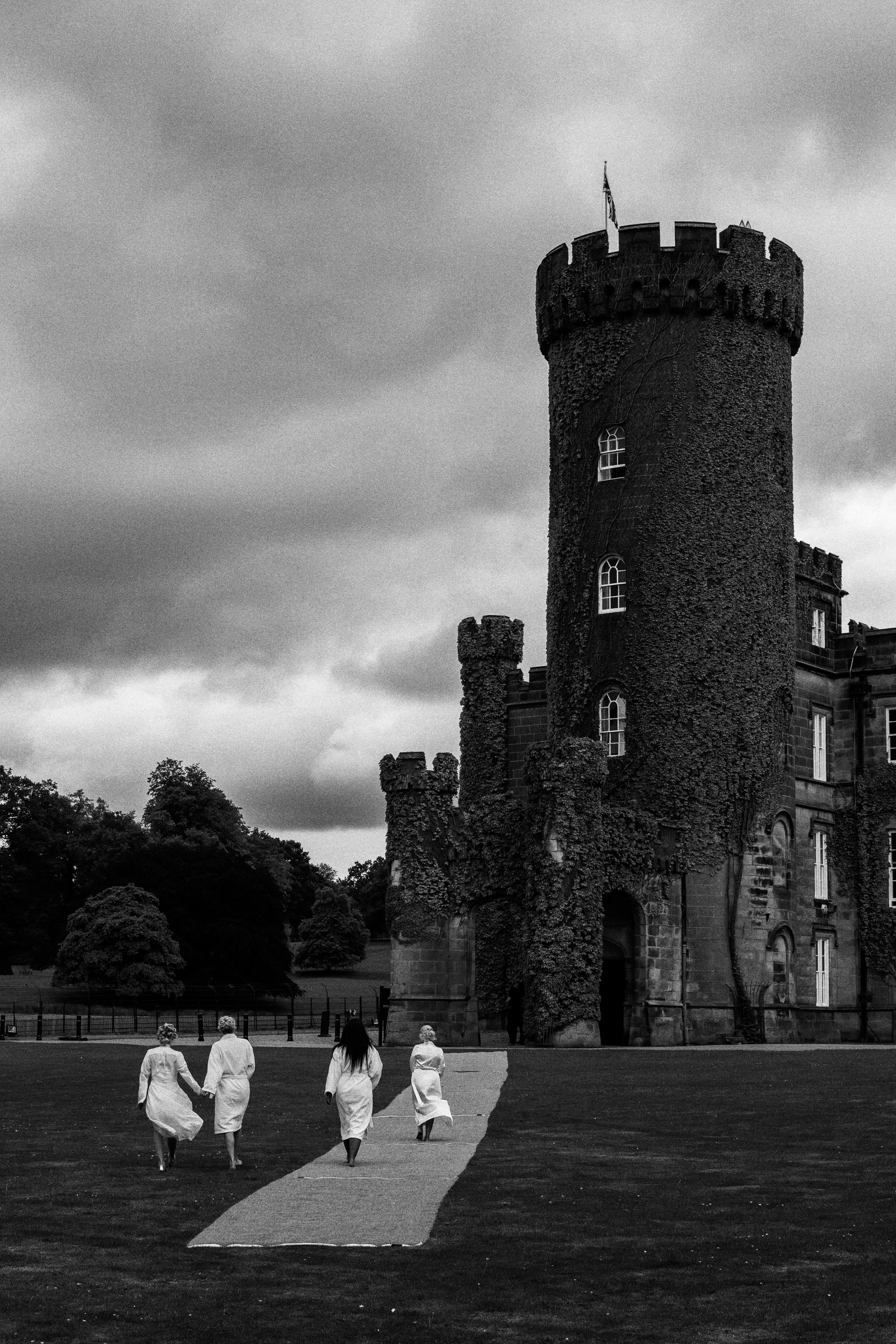 bridesmaids approach English castle in white robes - photo by Jeff Ascough