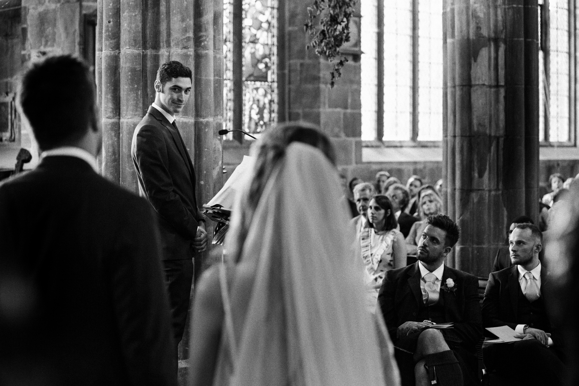 Brother looks toward bride during ceremony - photo by Jeff Ascough
