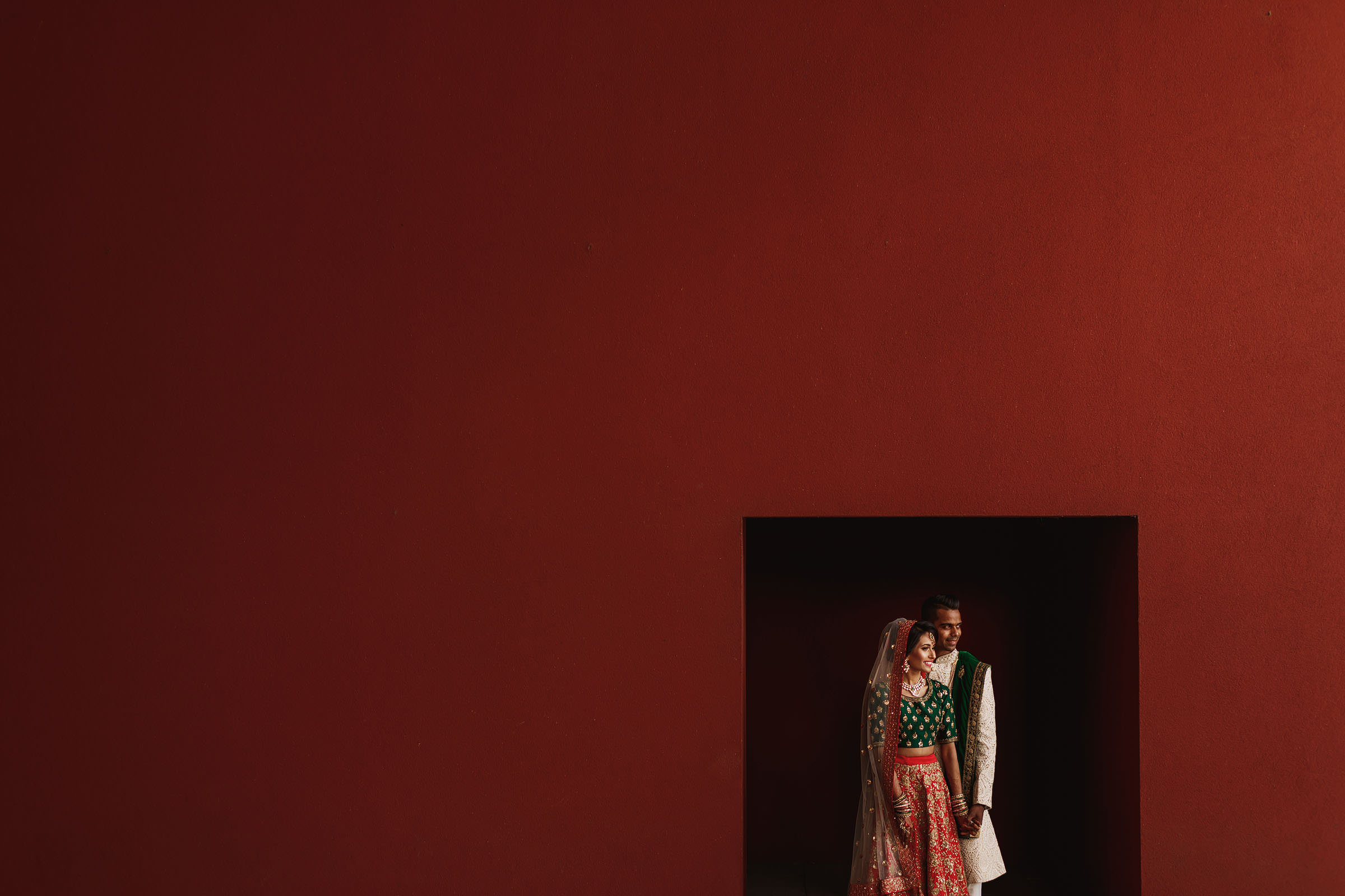 Couple in doorway against red wall - Photo by F5 Photography
