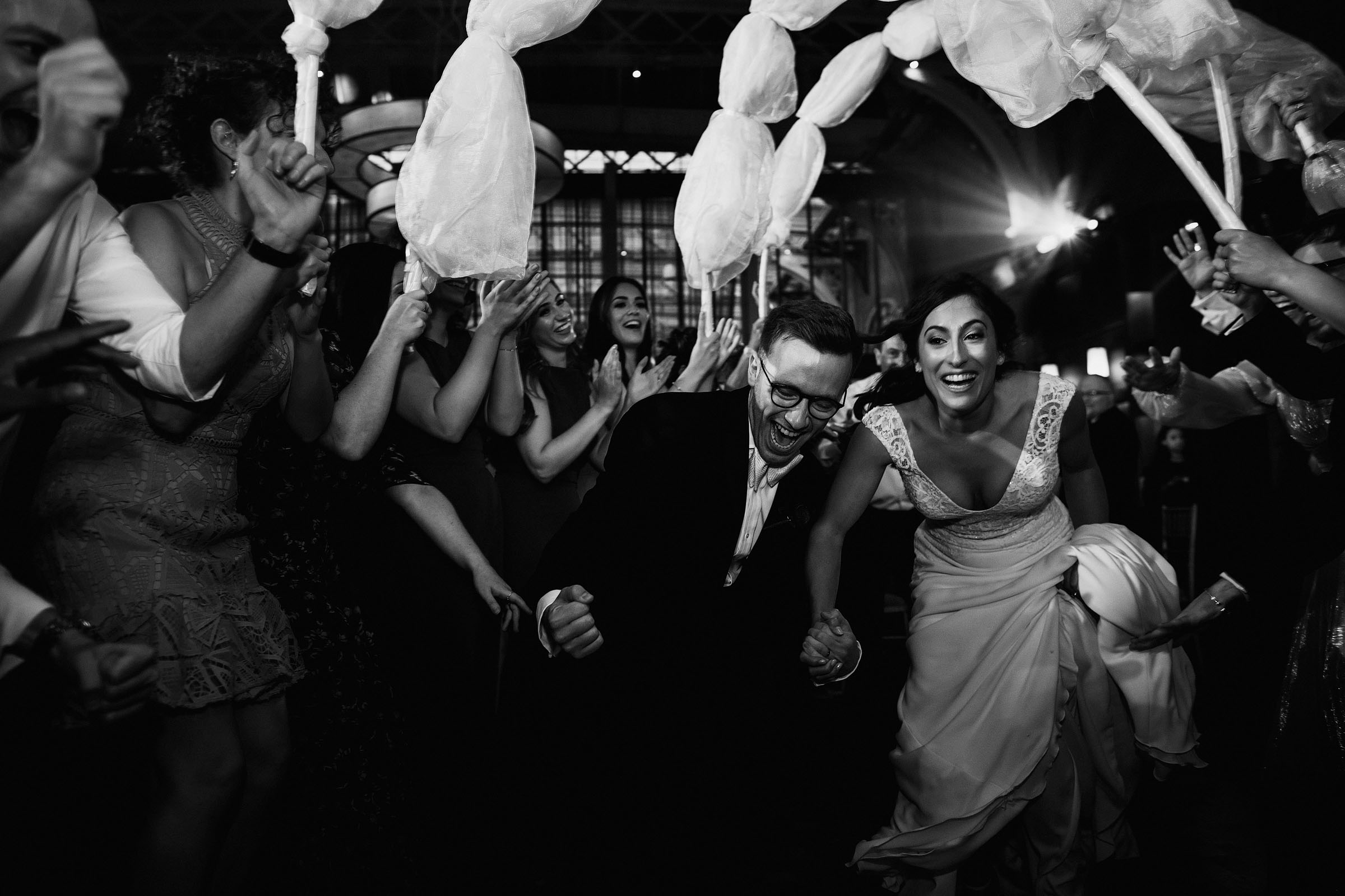 Couple running exit through guests - Photo by F5 Photography