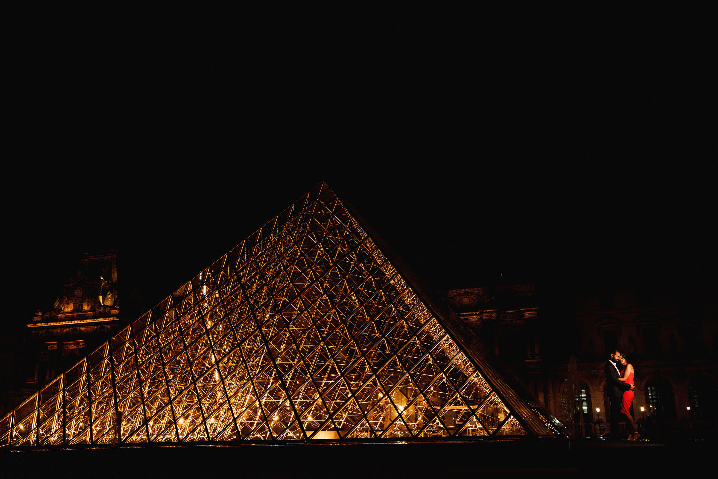 Elegant nighttime couple against louvre - Photo by F5 Photography