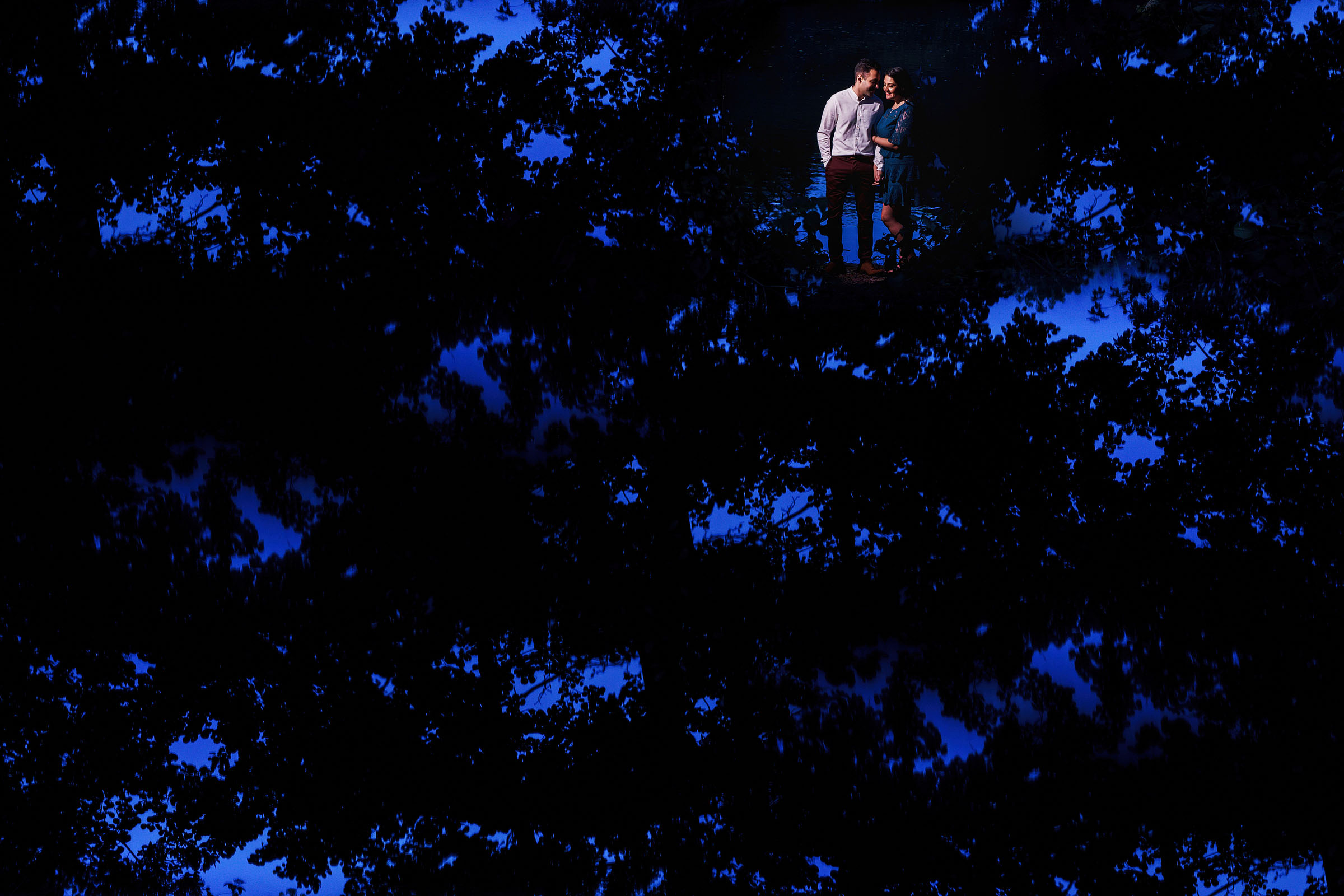 Engaged couple surrounded by reflection of trees and sky - photo by F5 Photography