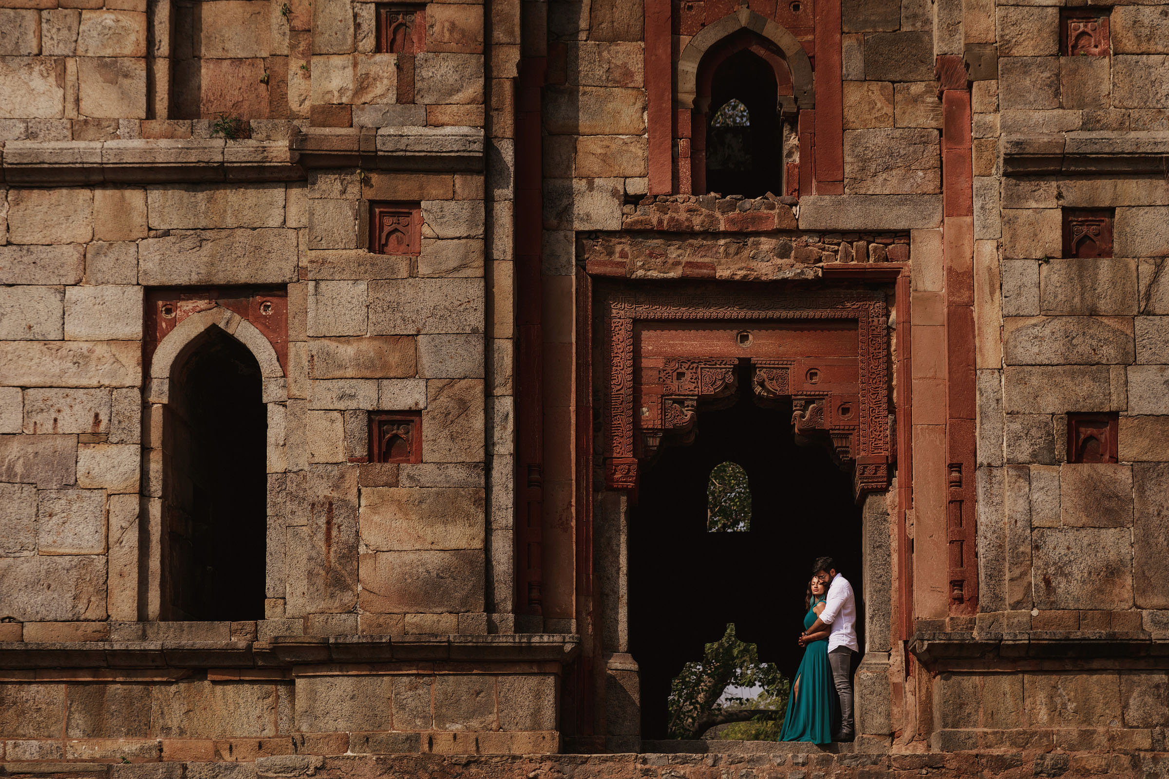 Engagement couple framed in historic doorway - Photo by F5 Photography