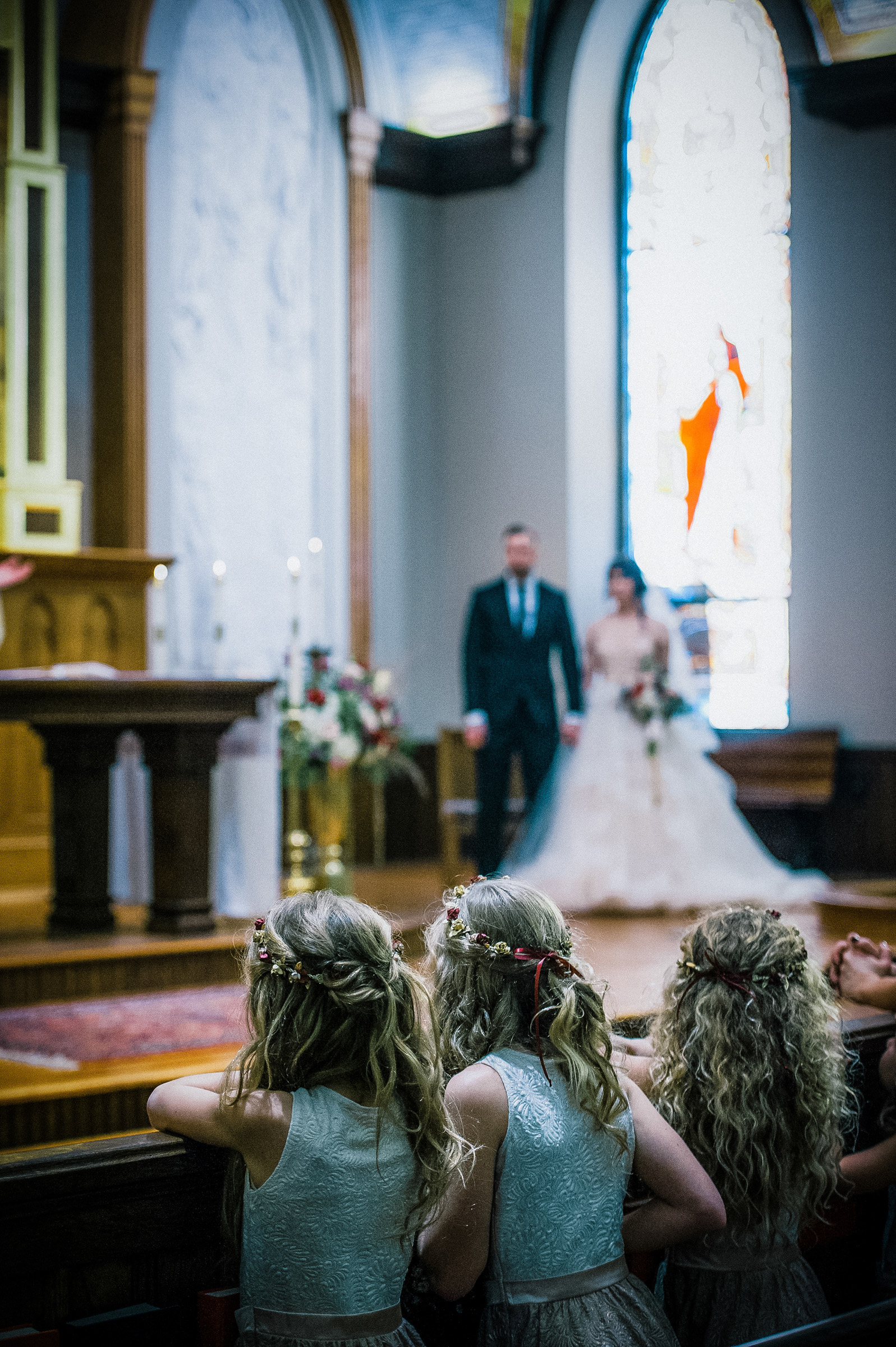 Flower girls watching wedding ceremony, by Richard Israel Photography
