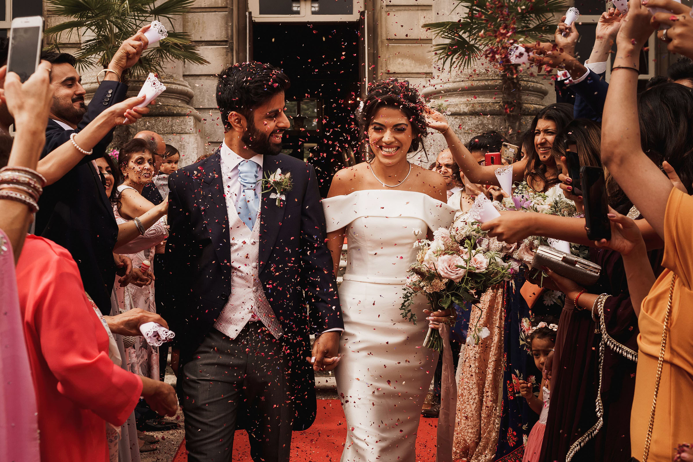 Happy couple exit amid confetti - Photo by F5 Photography