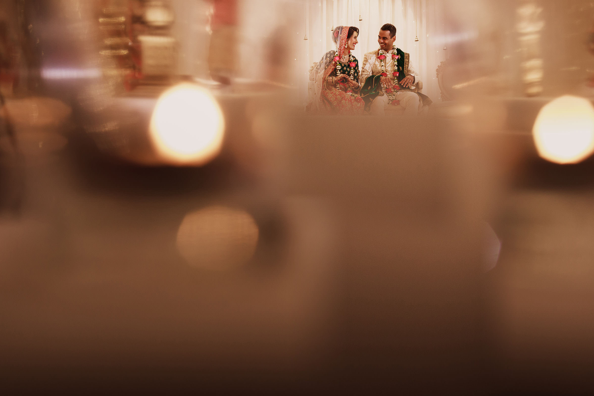 Indian bride and groom in bokeh frame. Photo by F5 Photography