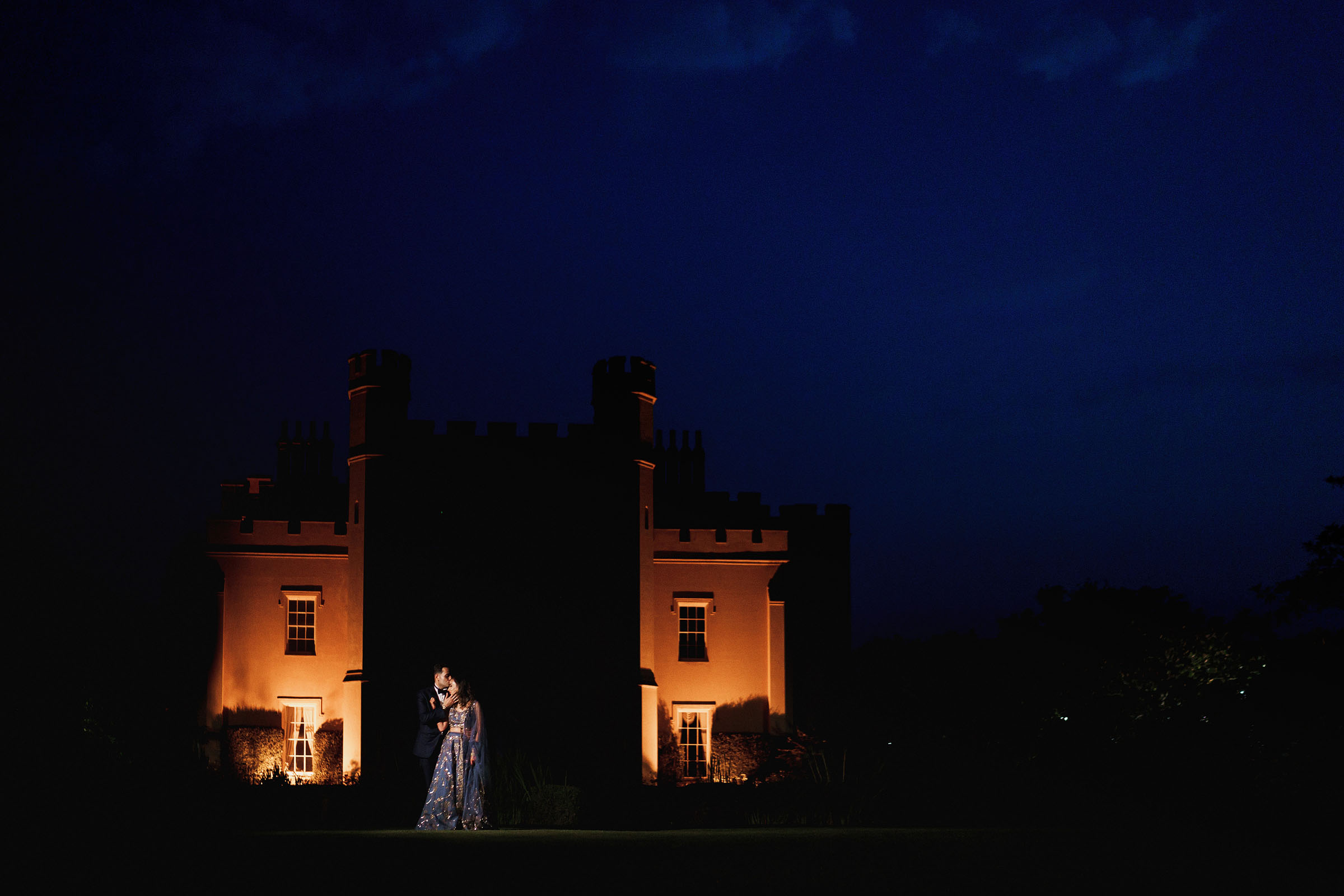 Nighttime couple against historic building - Photo by F5 Photography