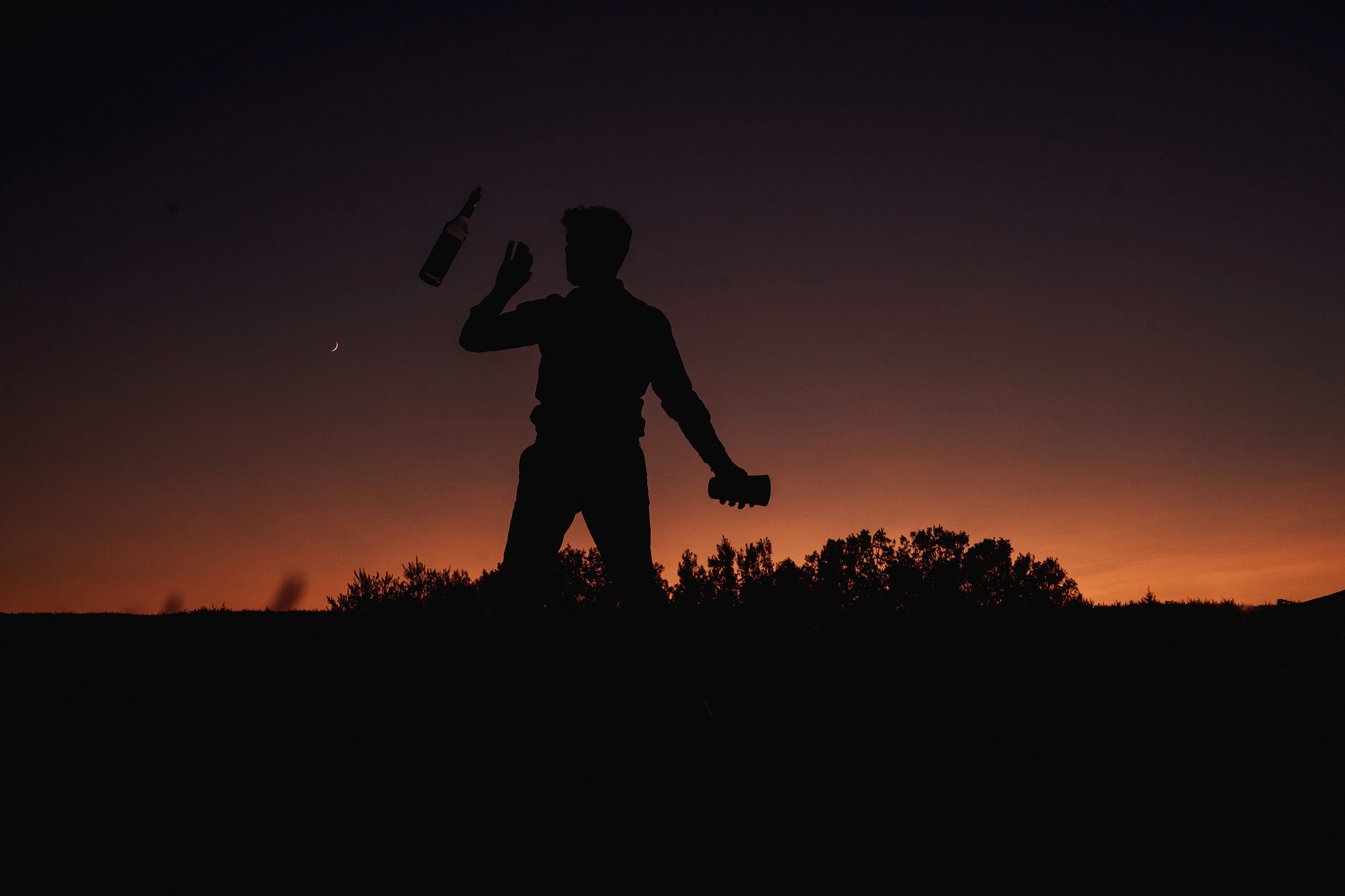 Sunset silhouette and guest catching bottle - Photo by F5 Photography