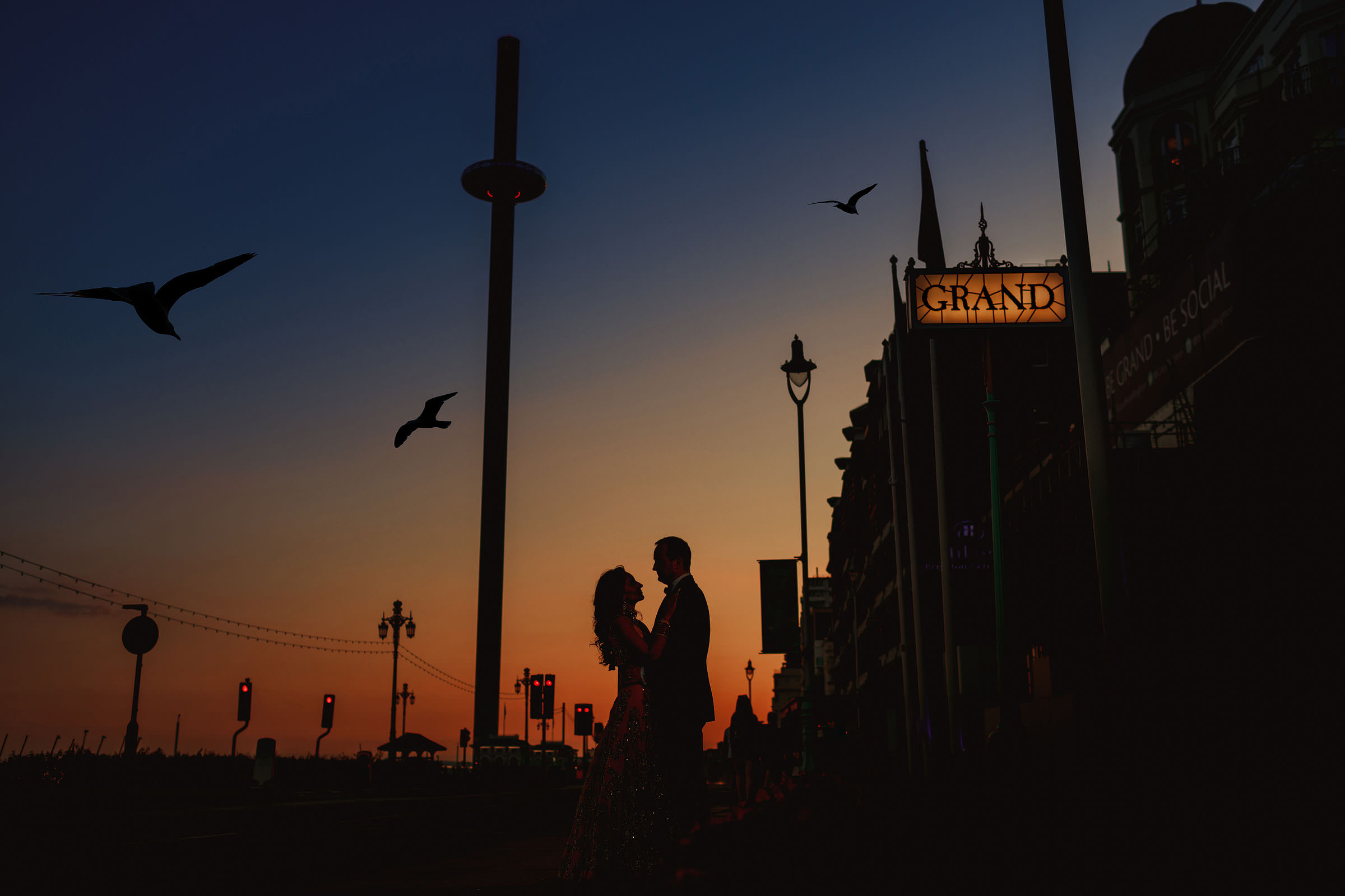 Sunset silhouette couple with grand sign - Photo by F5 Photography