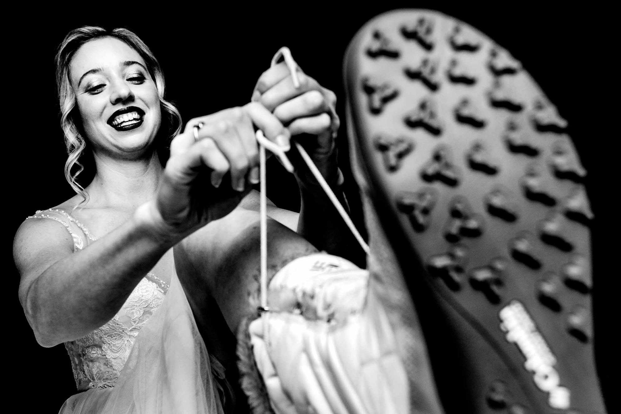 Smiling bride lacing up boots - photo by JOS & TREE