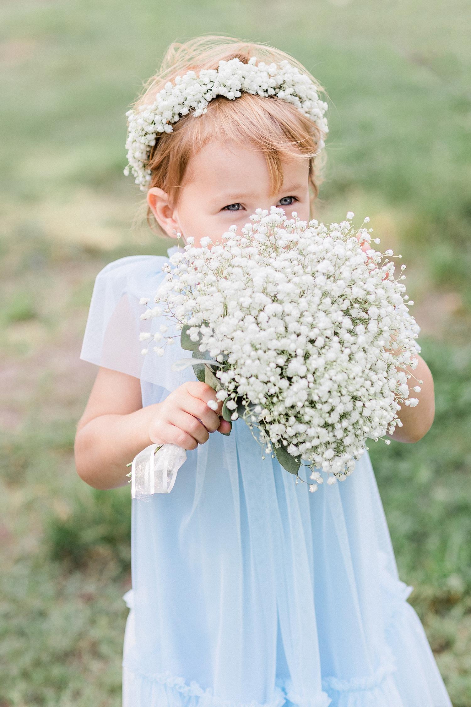 Flower girl holding bunch of baby's breath - photo by Jurgita Lukos Photography