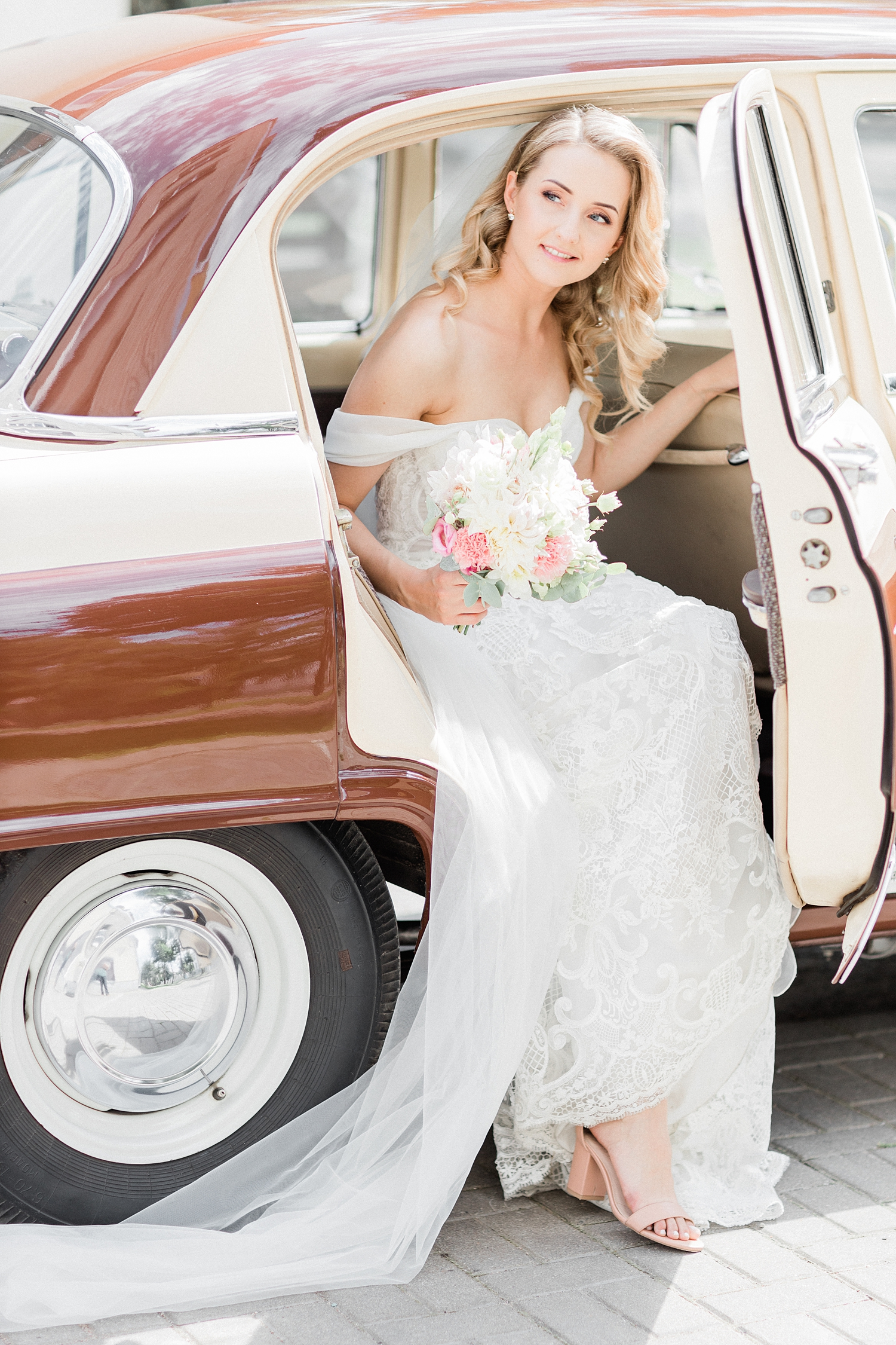 Bride with lace off-shoulder gown arrives in vintage car - photo by Jurgita Lukos Photography