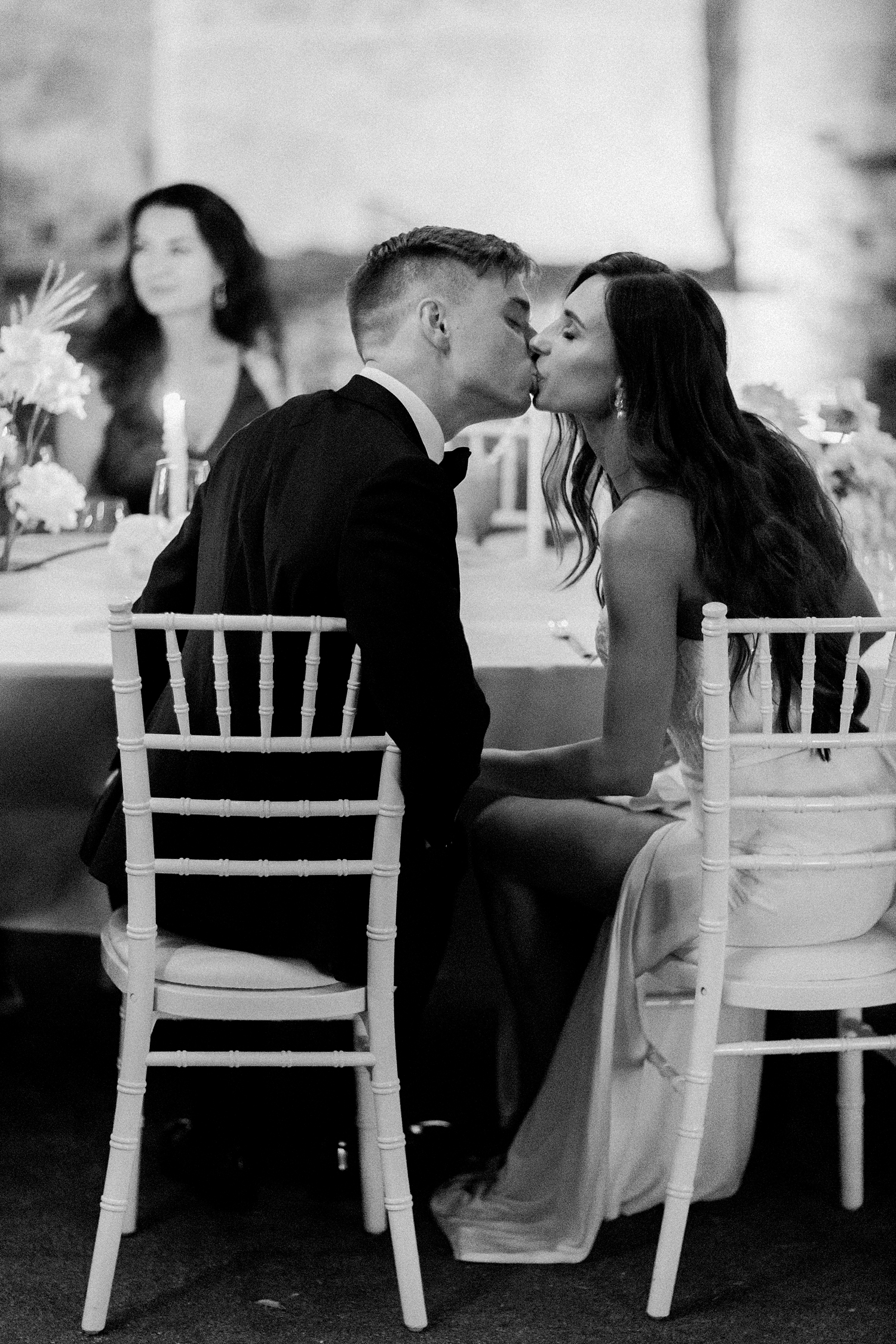 Couple kiss at head table - photo by Jurgita Lukos Photography