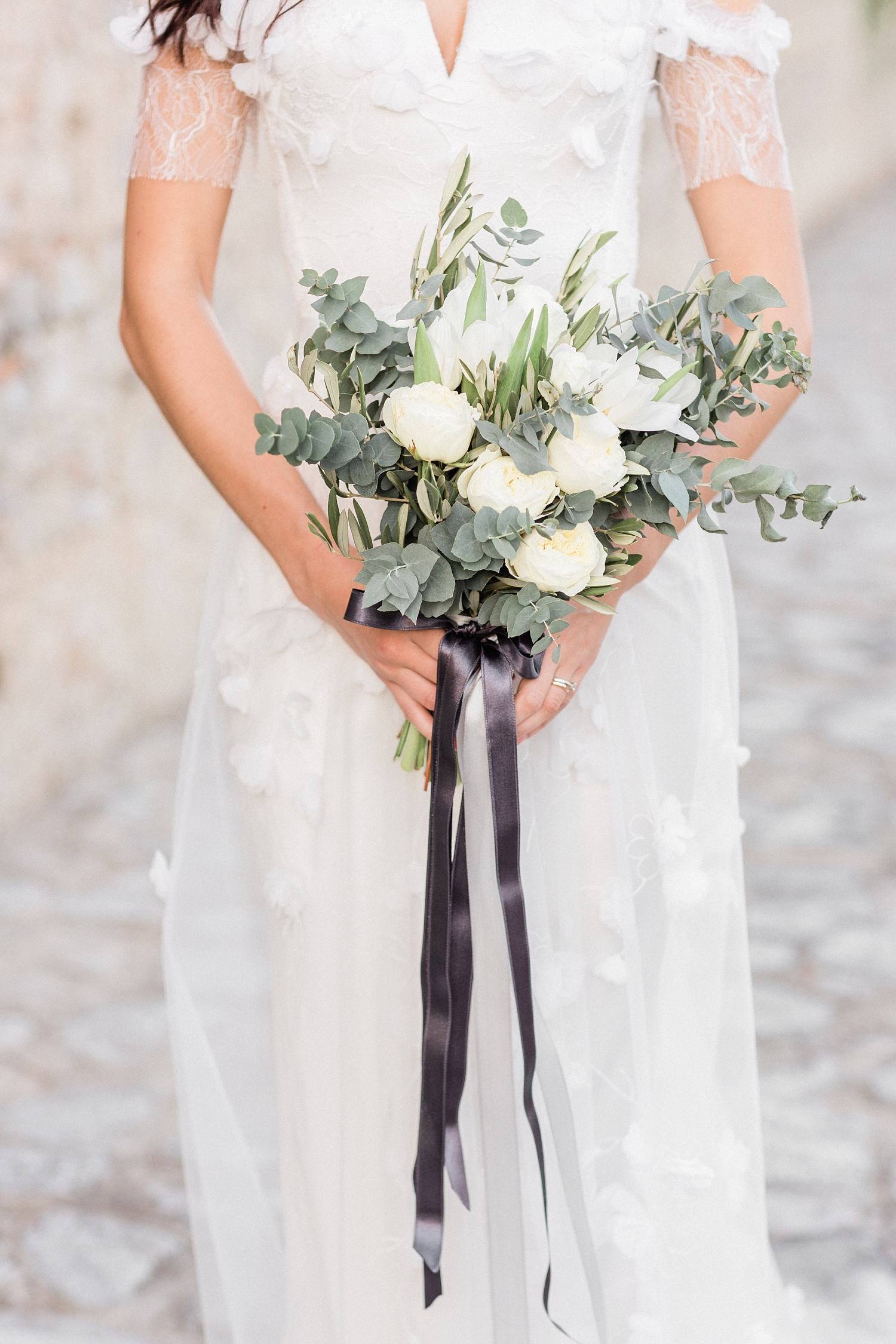Bride holding white rose bouquet with taupe satin ribbon - photo by Jurgita Lukos Photography