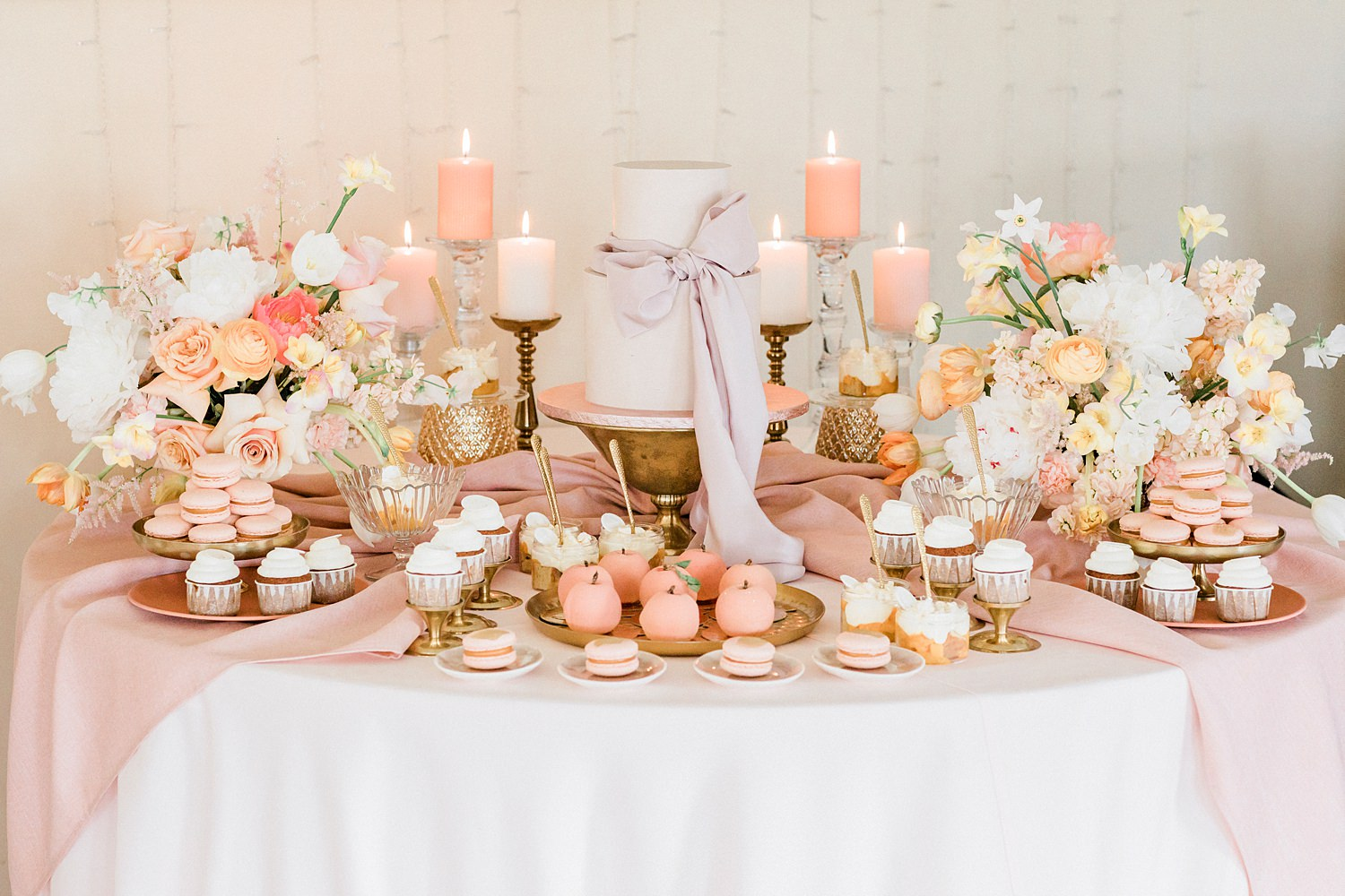 Dessert table featuring macarons and cupcakes with candles- photo by Jurgita Lukos Photography