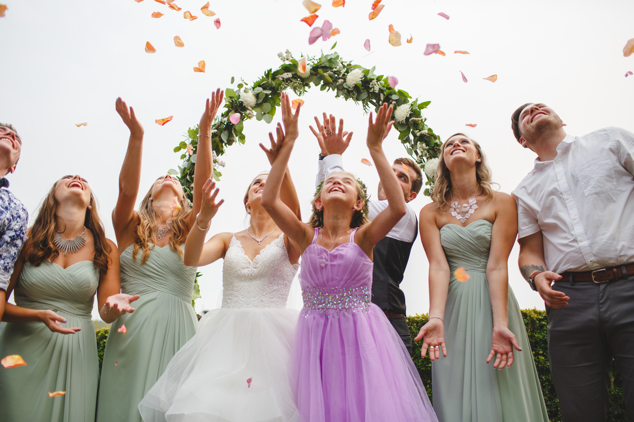 Bridal party raise hands to shower of petals - photo by Satya Curcio Photography