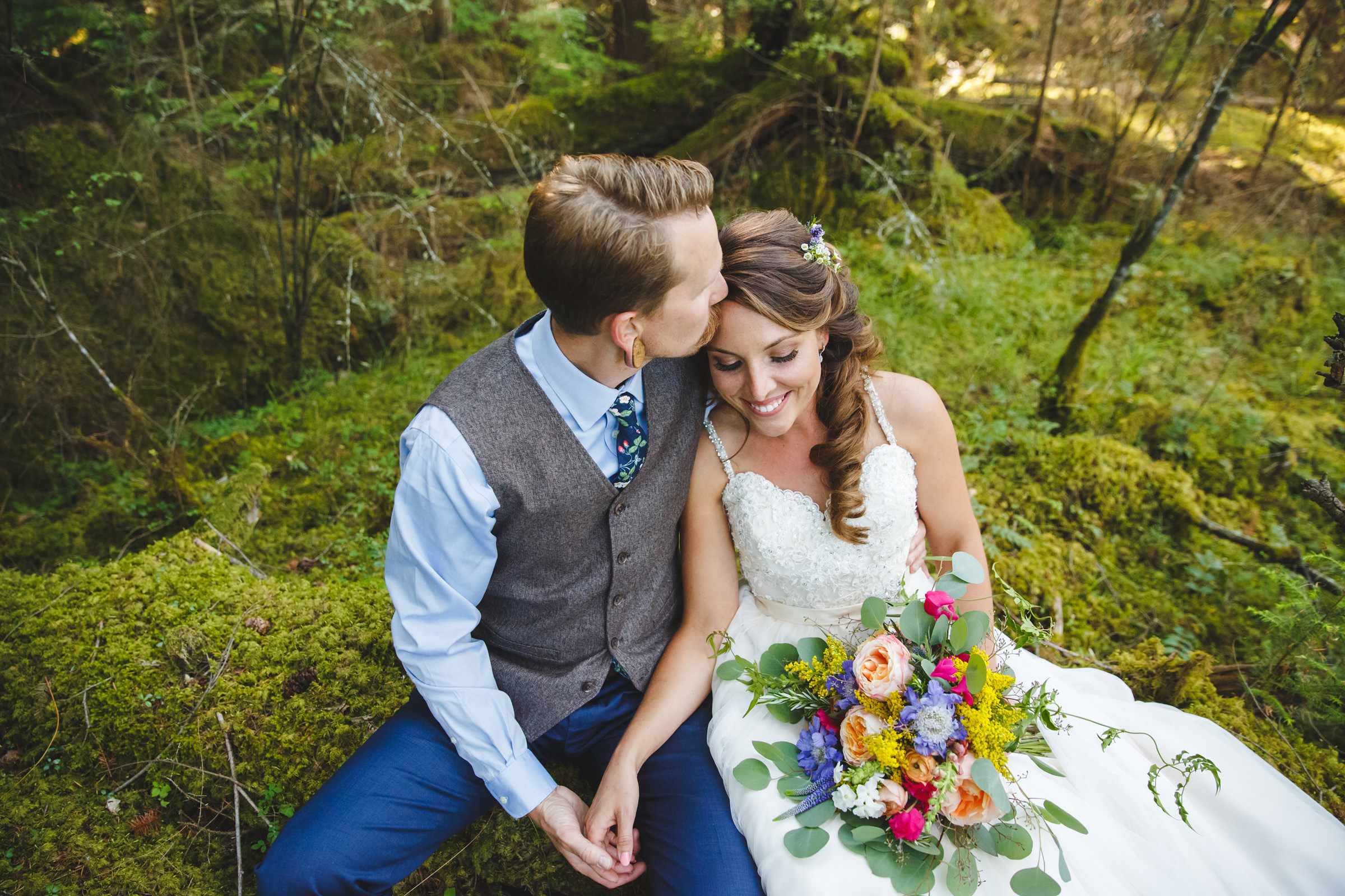 Bride and groom in mossy forest - photo by Satya Curcio Photography