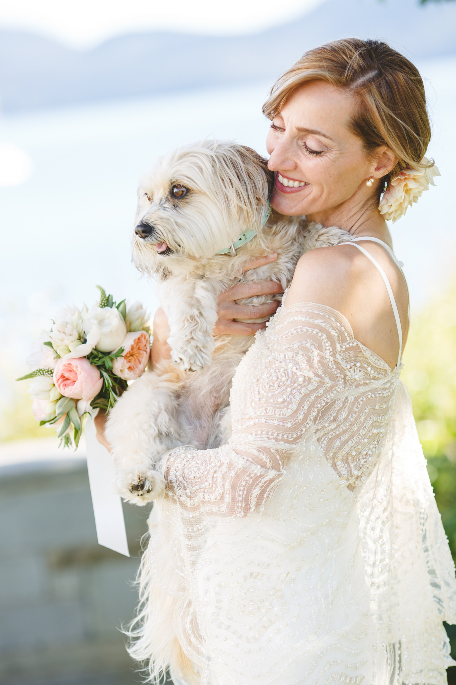 Bride holding fluffy white dog - photo by Satya Curcio Photography