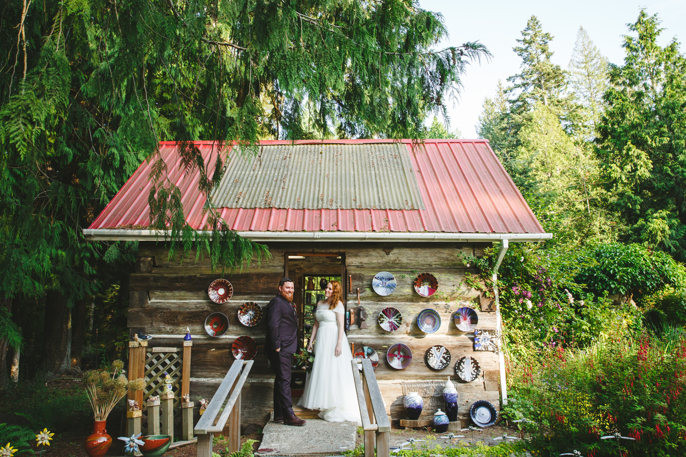 Couple outside rustic log cabin - photo by Satya Curcio Photography