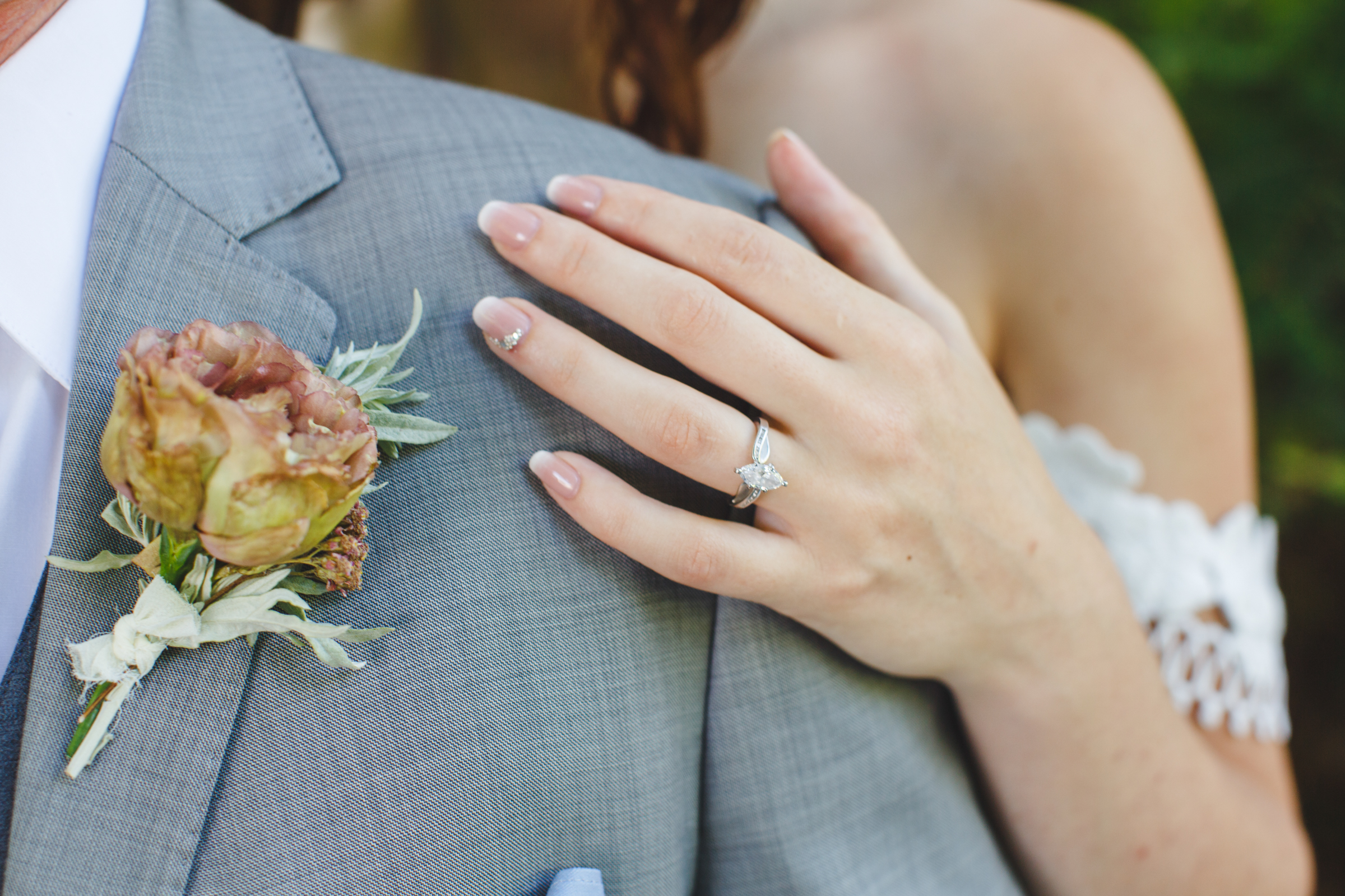 Detail of grooms boutonniere and brides ring - photo by Satya Curcio Photography