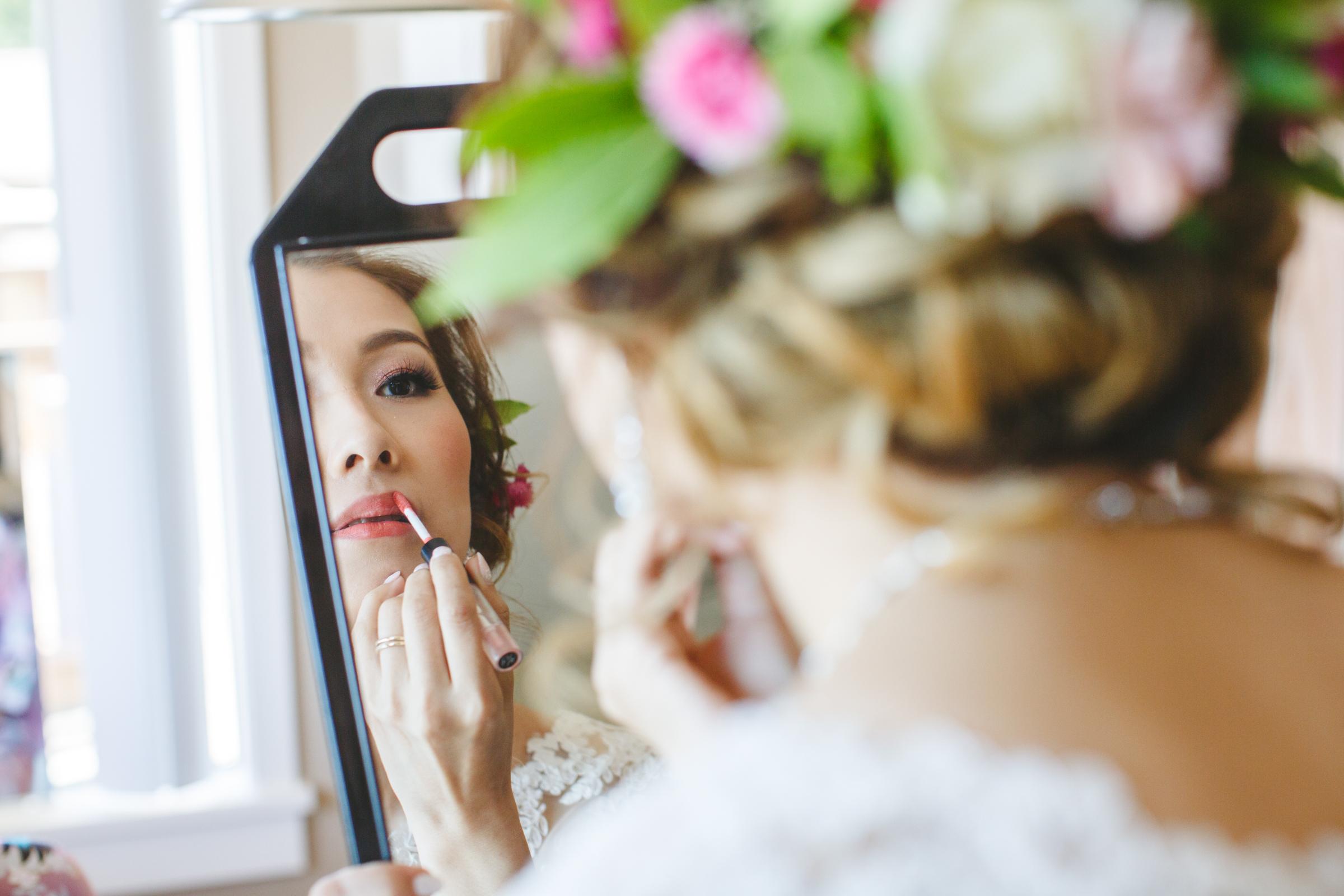 reflected bride applying lipstick- photo by Satya Curcio Photography