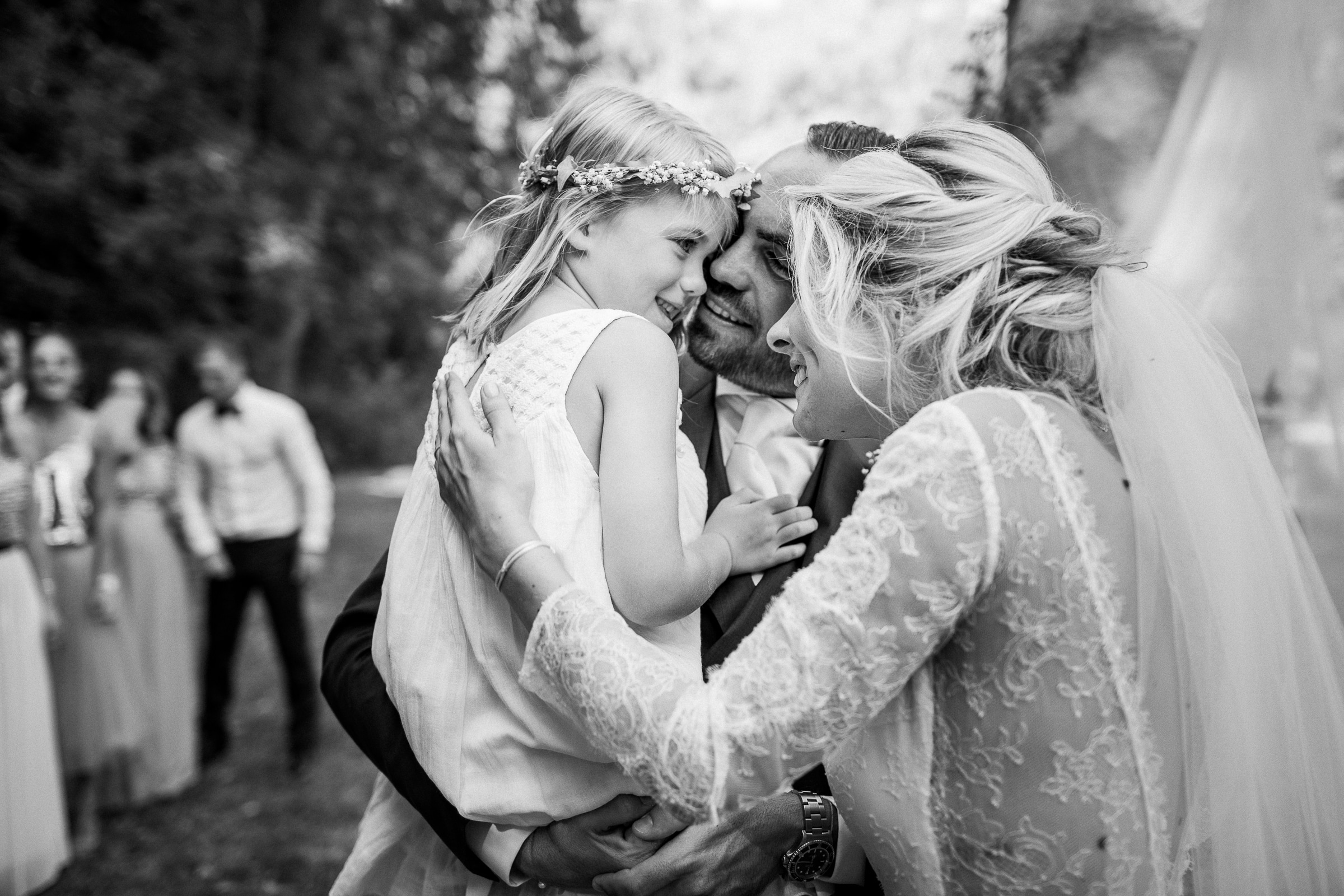 Bride and groom hold flower girl - photo by Sylvain Bouzat Wedding Photographer