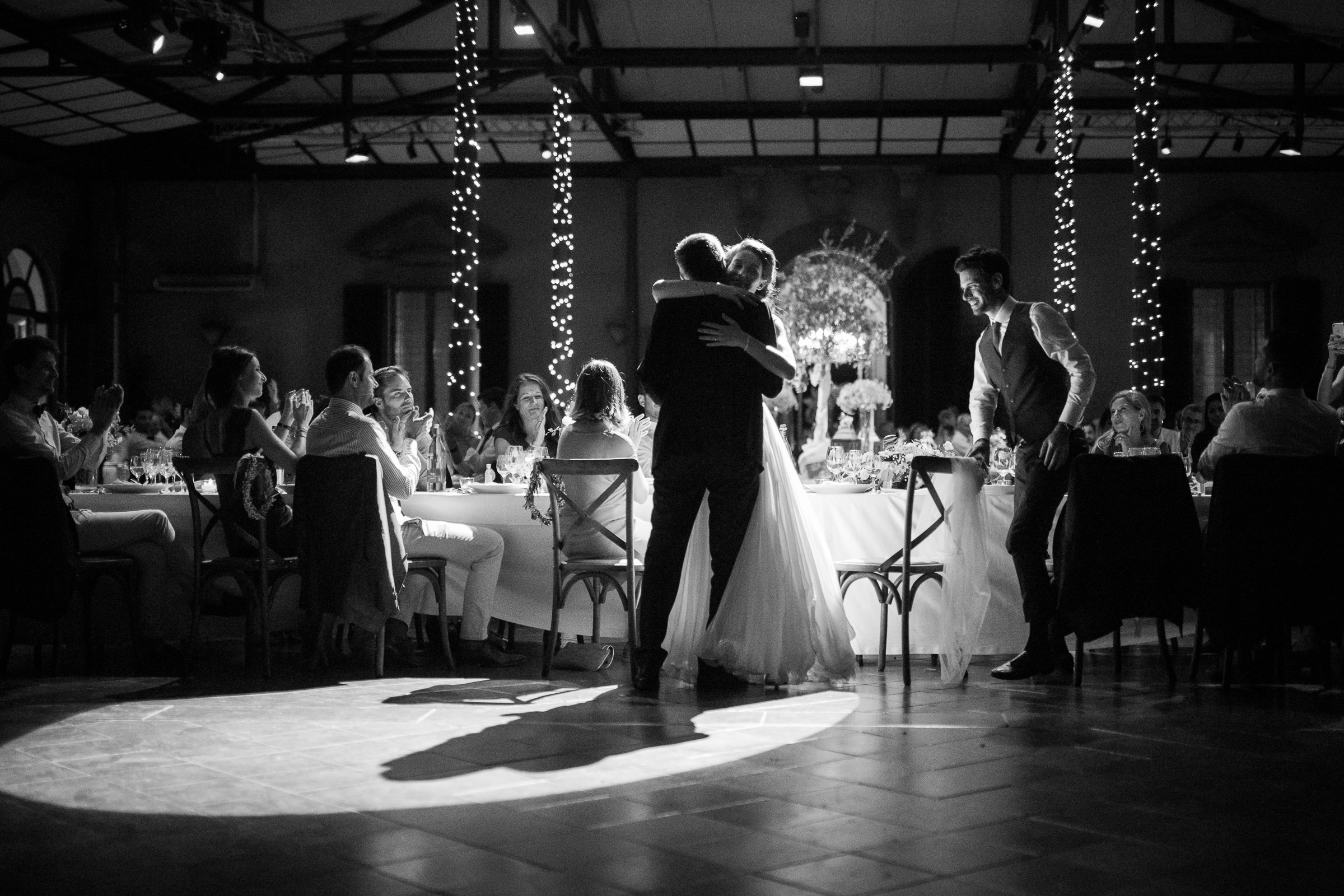 Bride stands to hug father at wedding table - photo by Sylvain Bouzat Wedding Photographer
