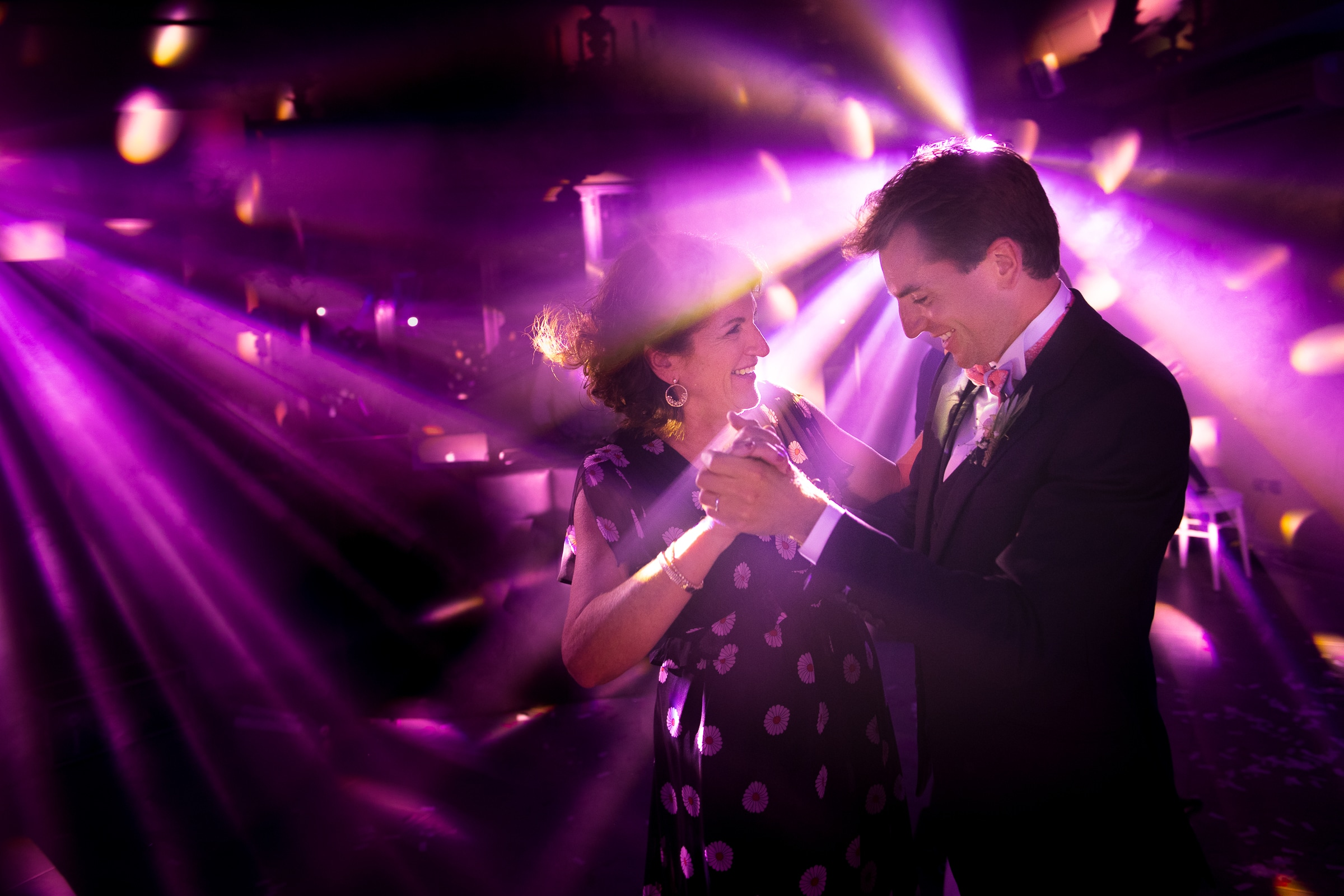 Couple dancing in purple light - photo by Sylvain Bouzat Wedding Photographer
