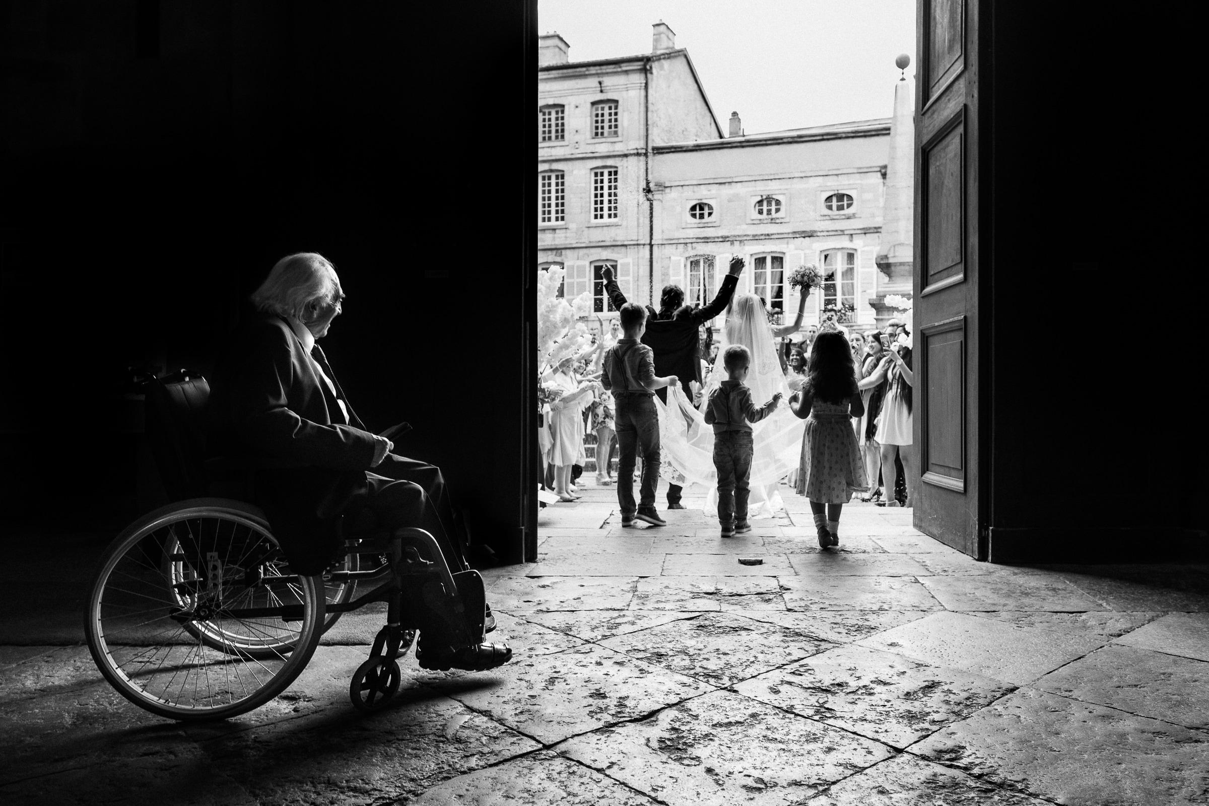 Grandfather watches through doorway couple celebrating in courtyard - photo by Sylvain Bouzat Wedding Photographer