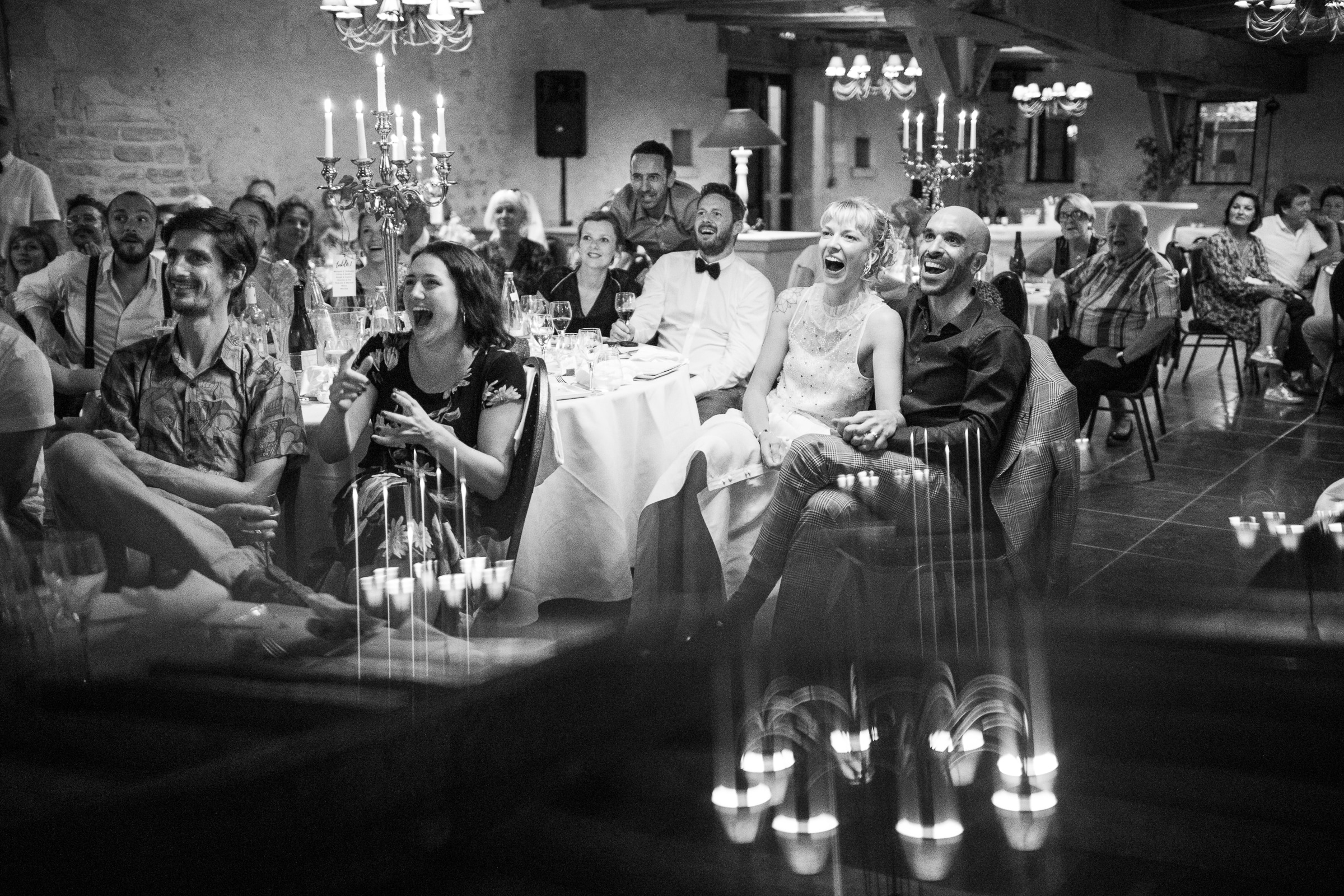 Guests share funny moment at reception - photo by Sylvain Bouzat Wedding Photographer